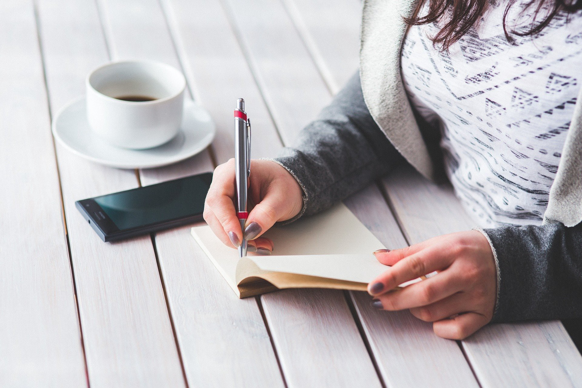 woman with coffee, phone, and notebook sitting at picnic table writing about what she's learned about herself through writing