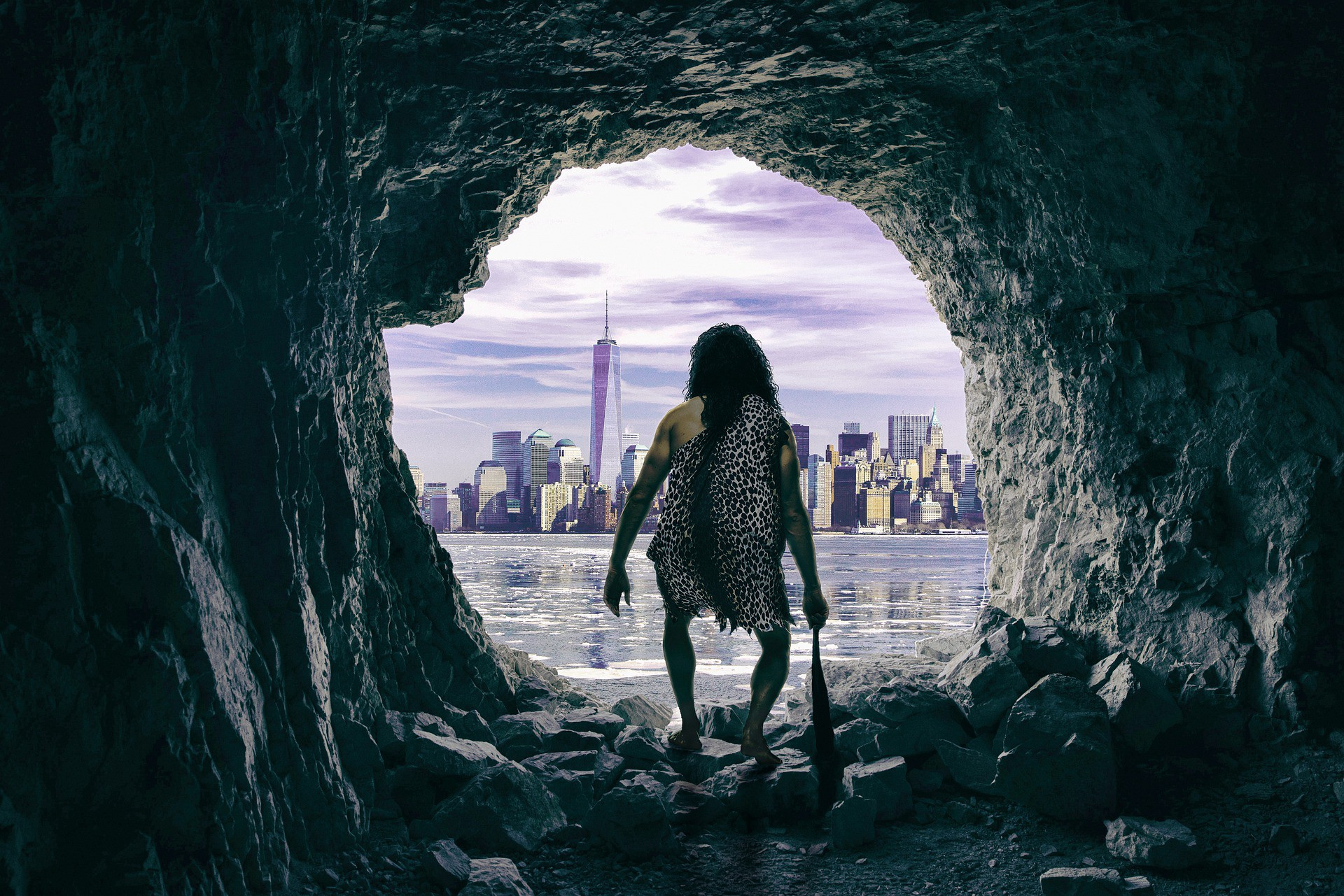 Cavewoman in a leopard skin with a club paused at the mouth of a cave, starting across a lake to a modern city.