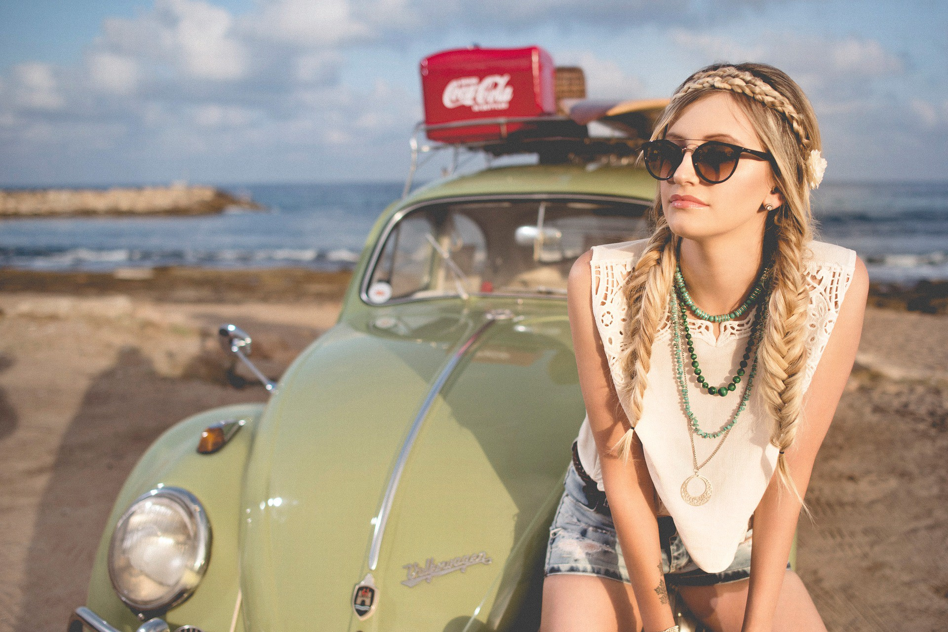 Young woman sitting on an old Volkswagen Bug. Write titles that people will click on.