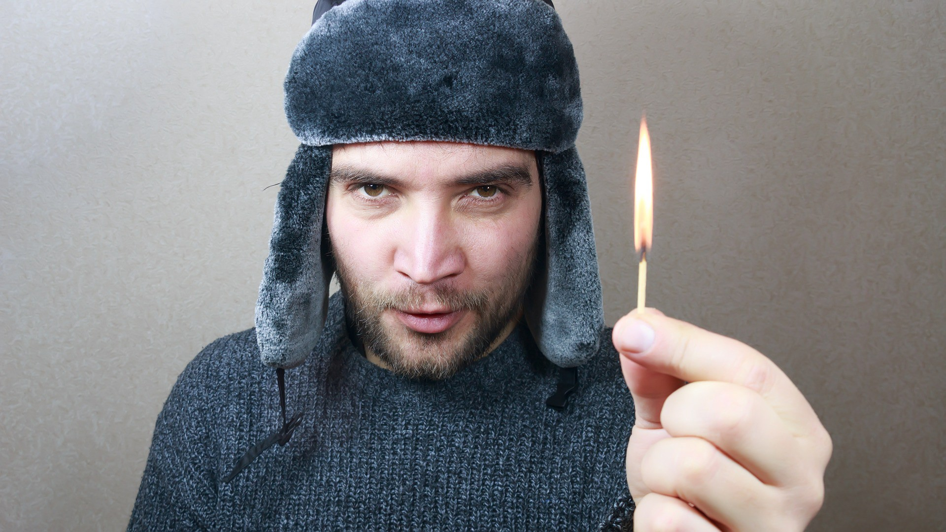 guy in winter hat with lit match
