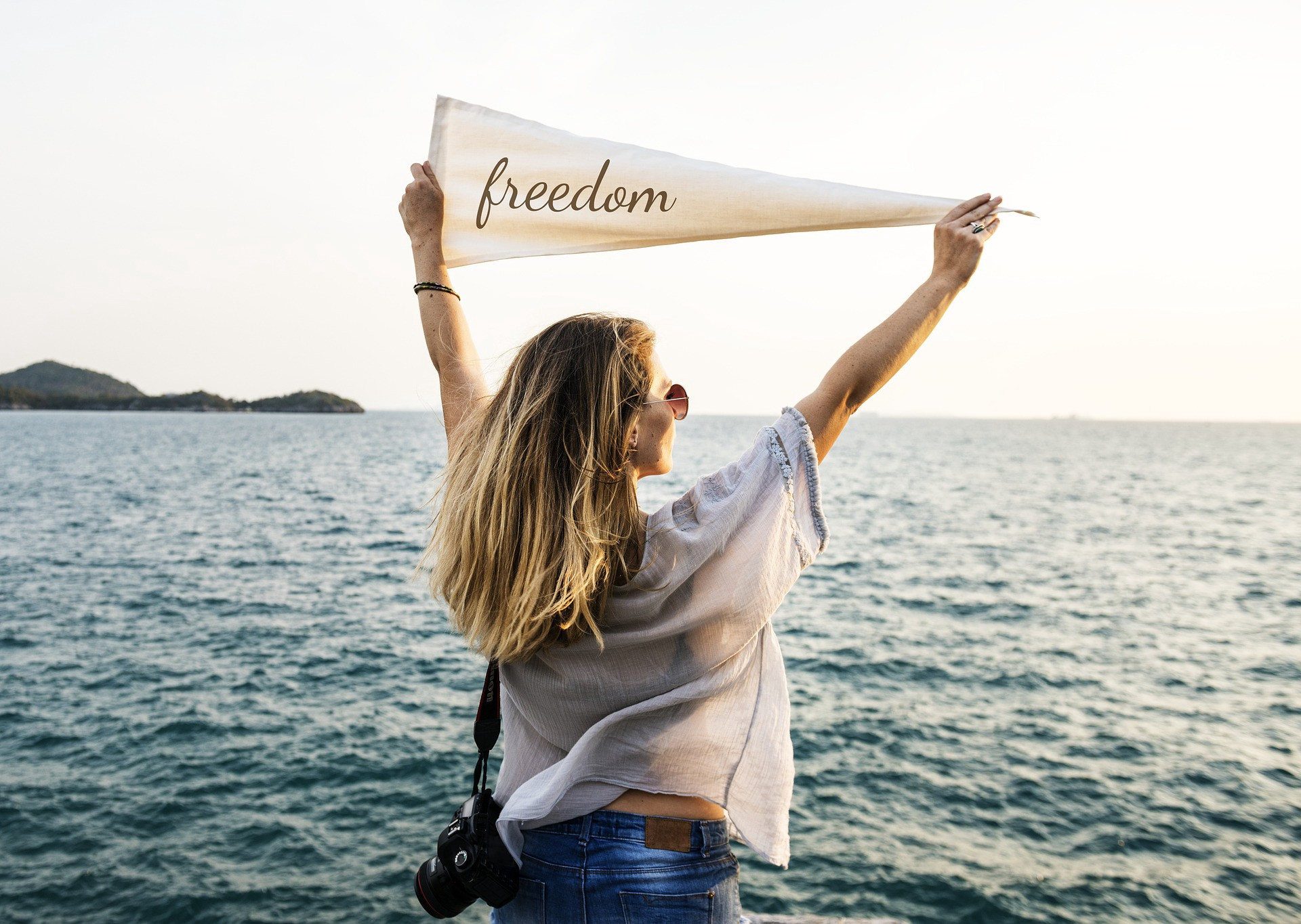 """Woman in water holding up a sign that says """"freedom""""."""
