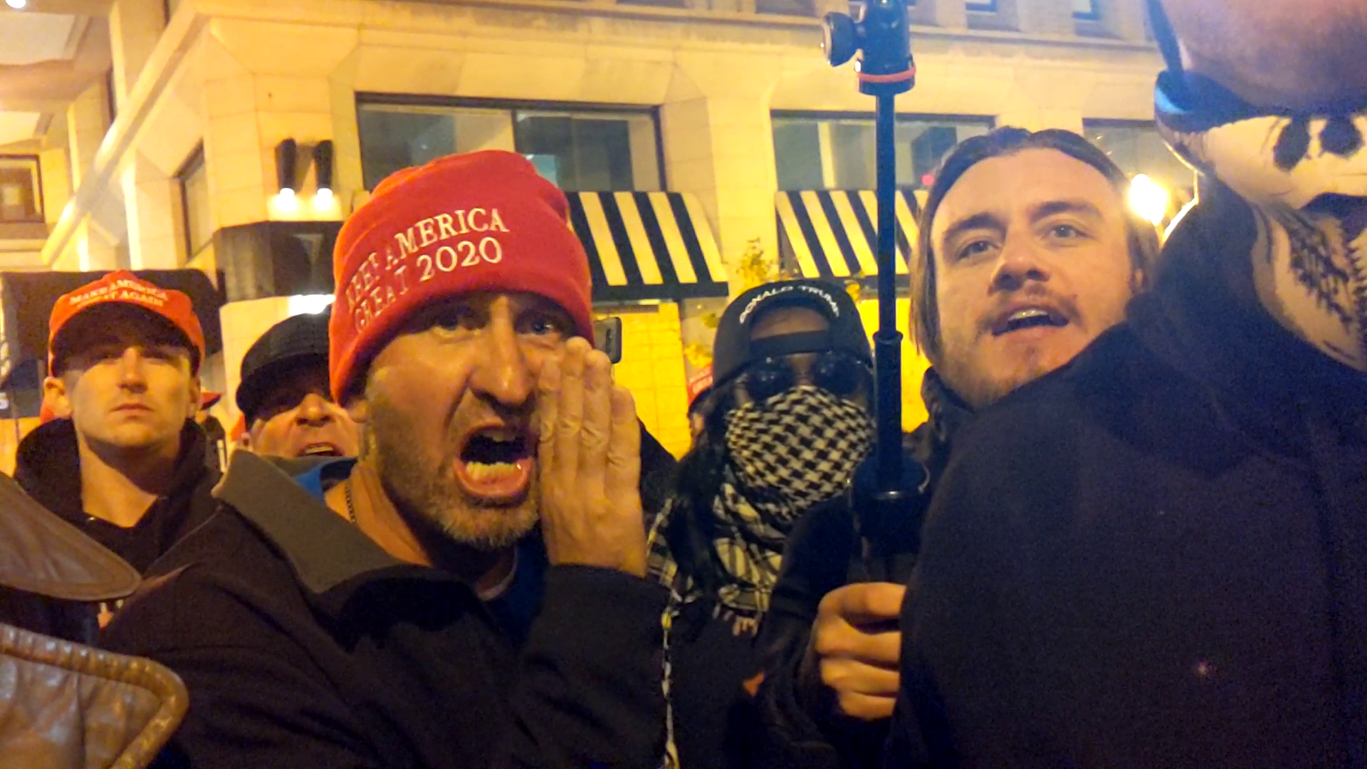 A crowd at night. A man in a red MAGA beanie yells something with his hand at the side of his face.
