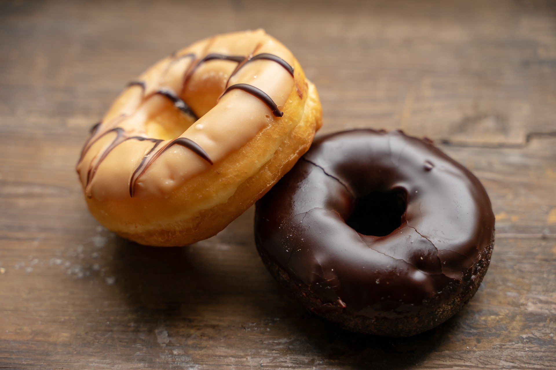 Two doughnuts on a wooden table