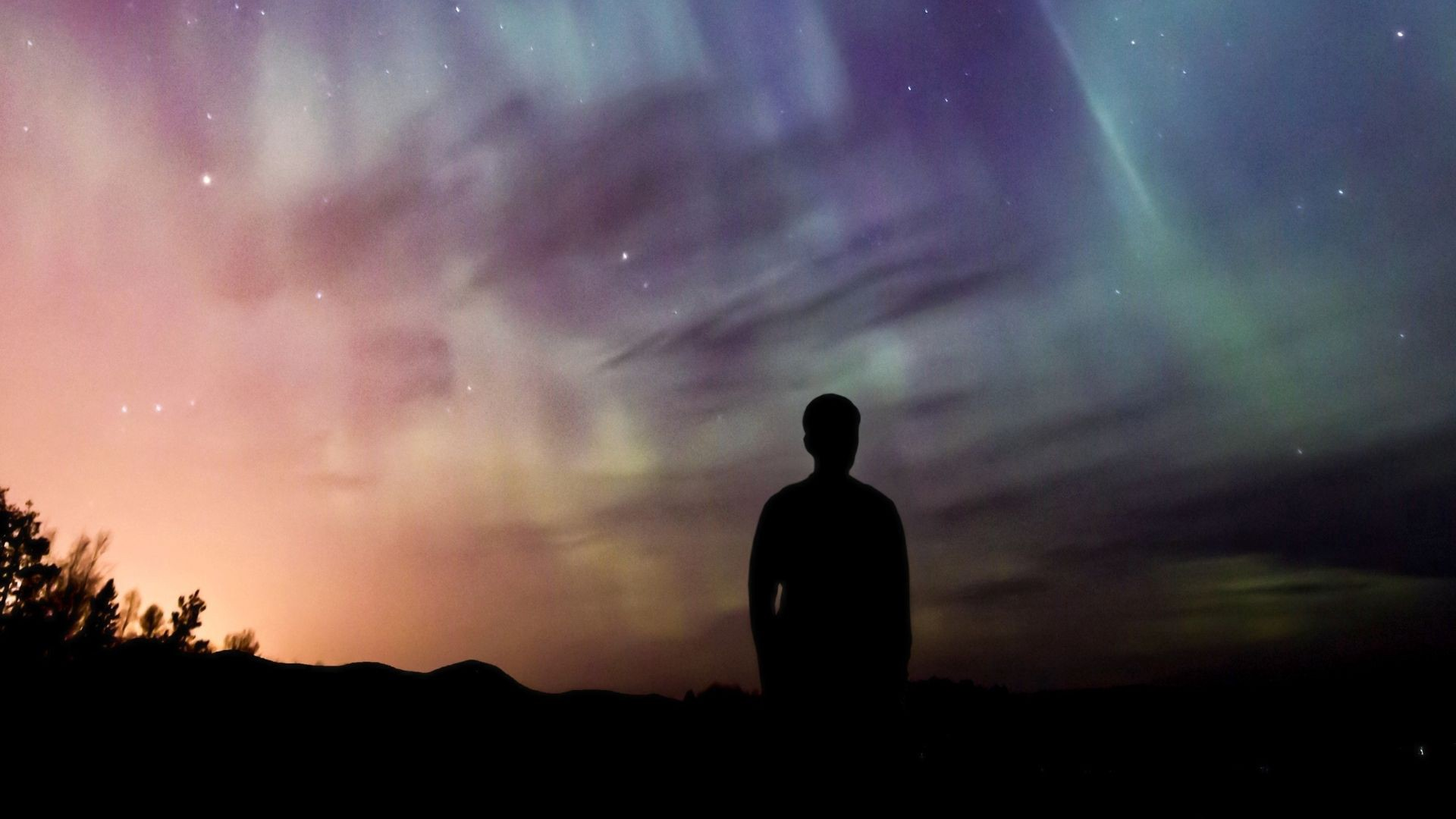 Silhouette of a person looking toward a colorful night sky
