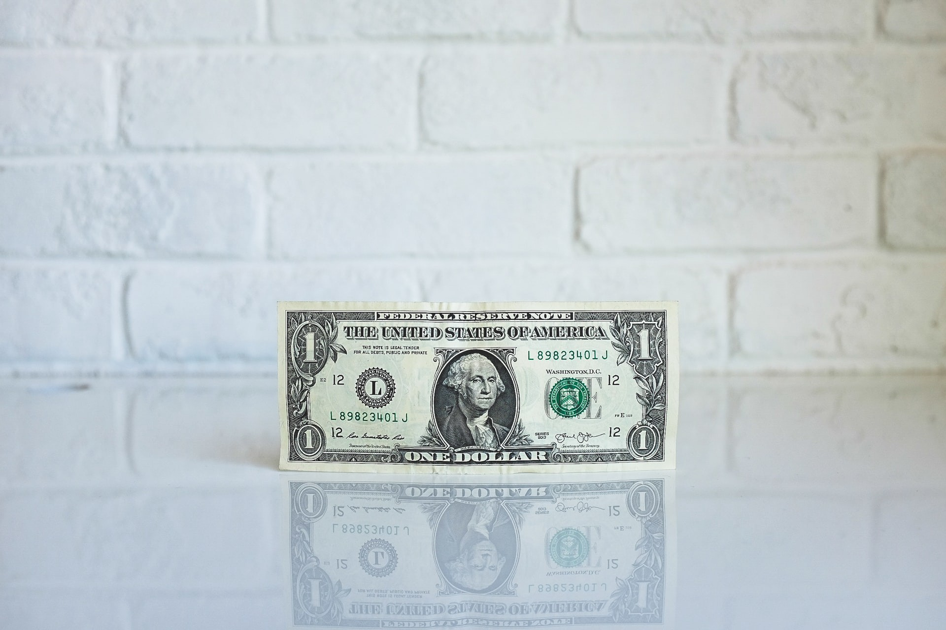 A single dollar bill in front of a white brick wall