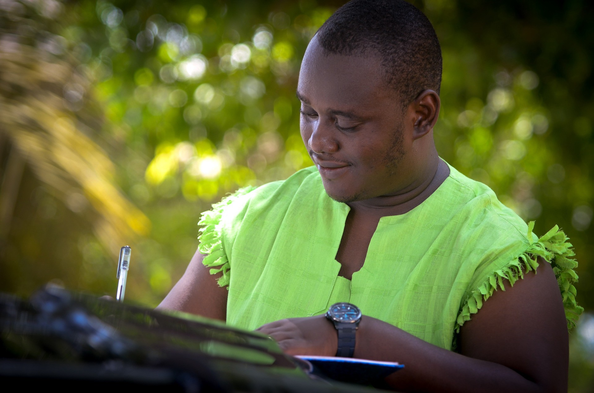 Black man in bright green shirt with frills writing.