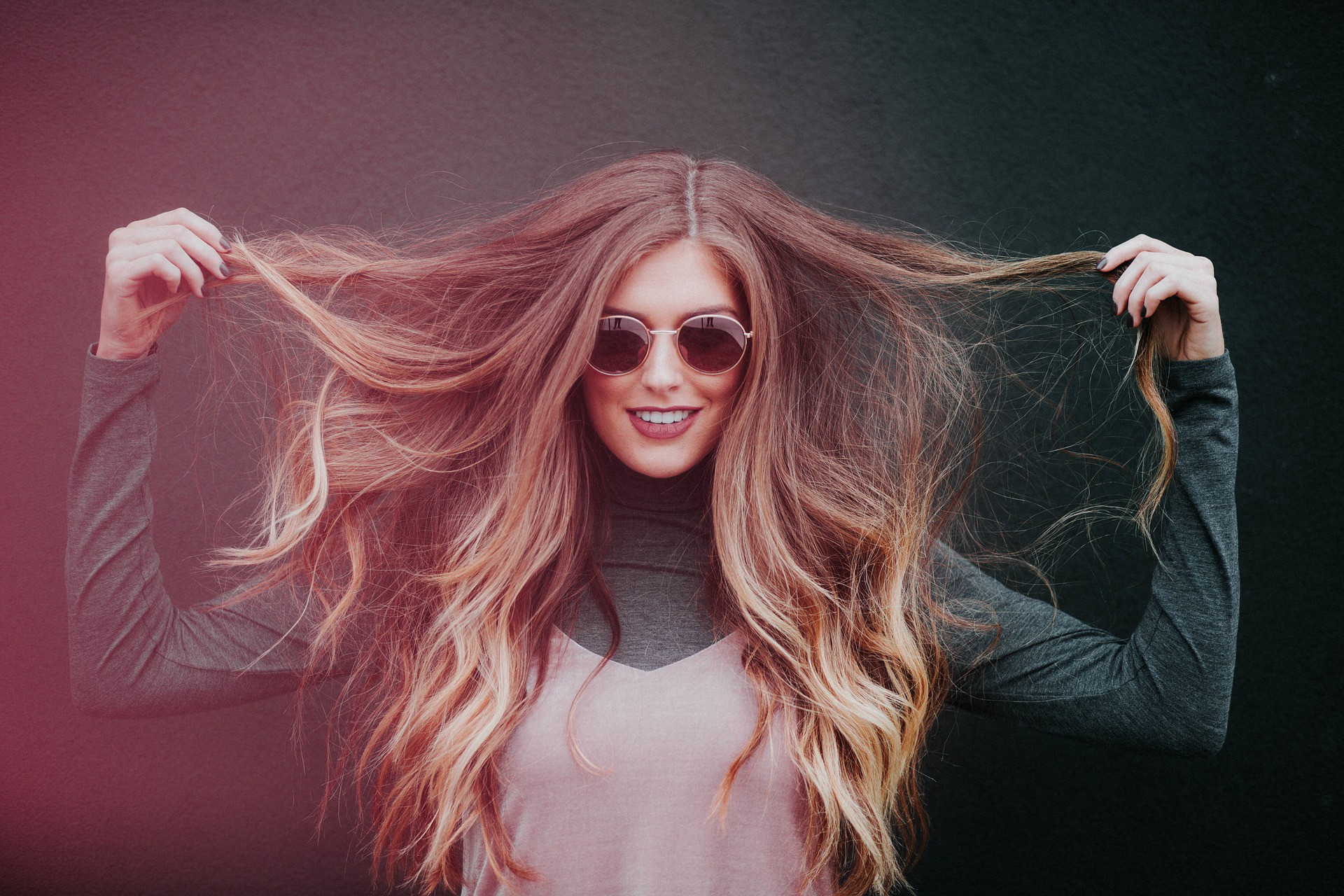 Woman in sun glasses with long hair holding her hair out