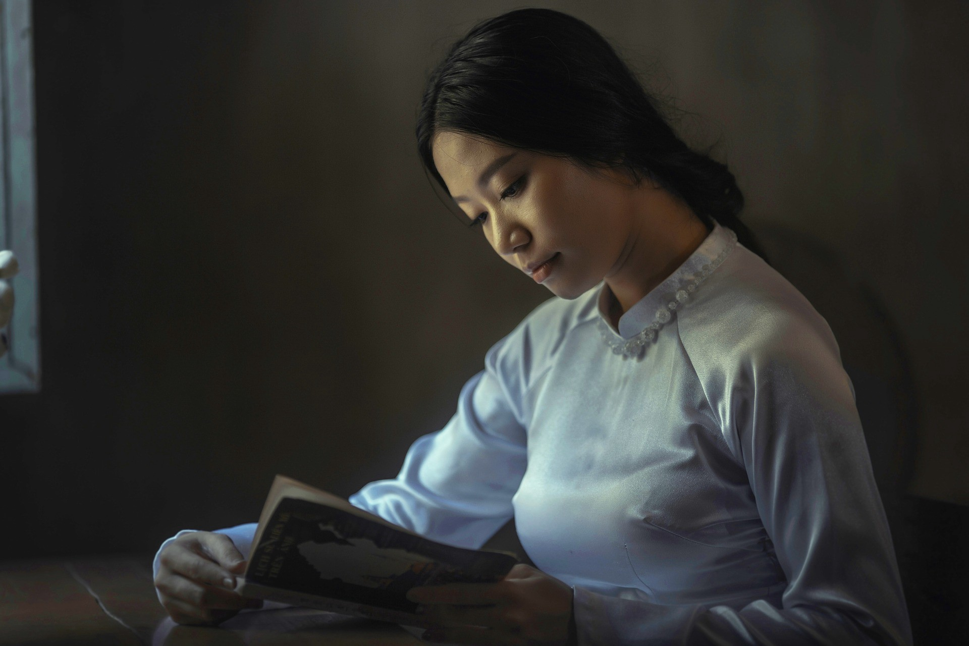 Young Asian woman in white blouse reads a book indoors.