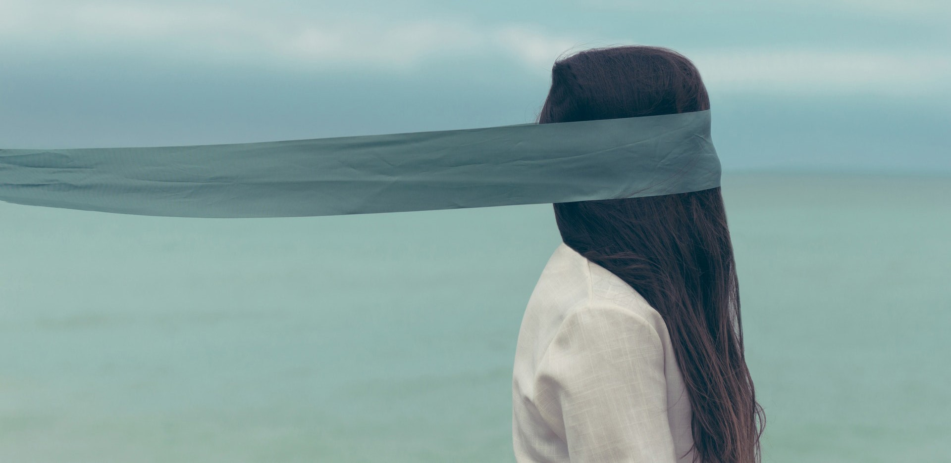 Blindfolded girl facing the sea.