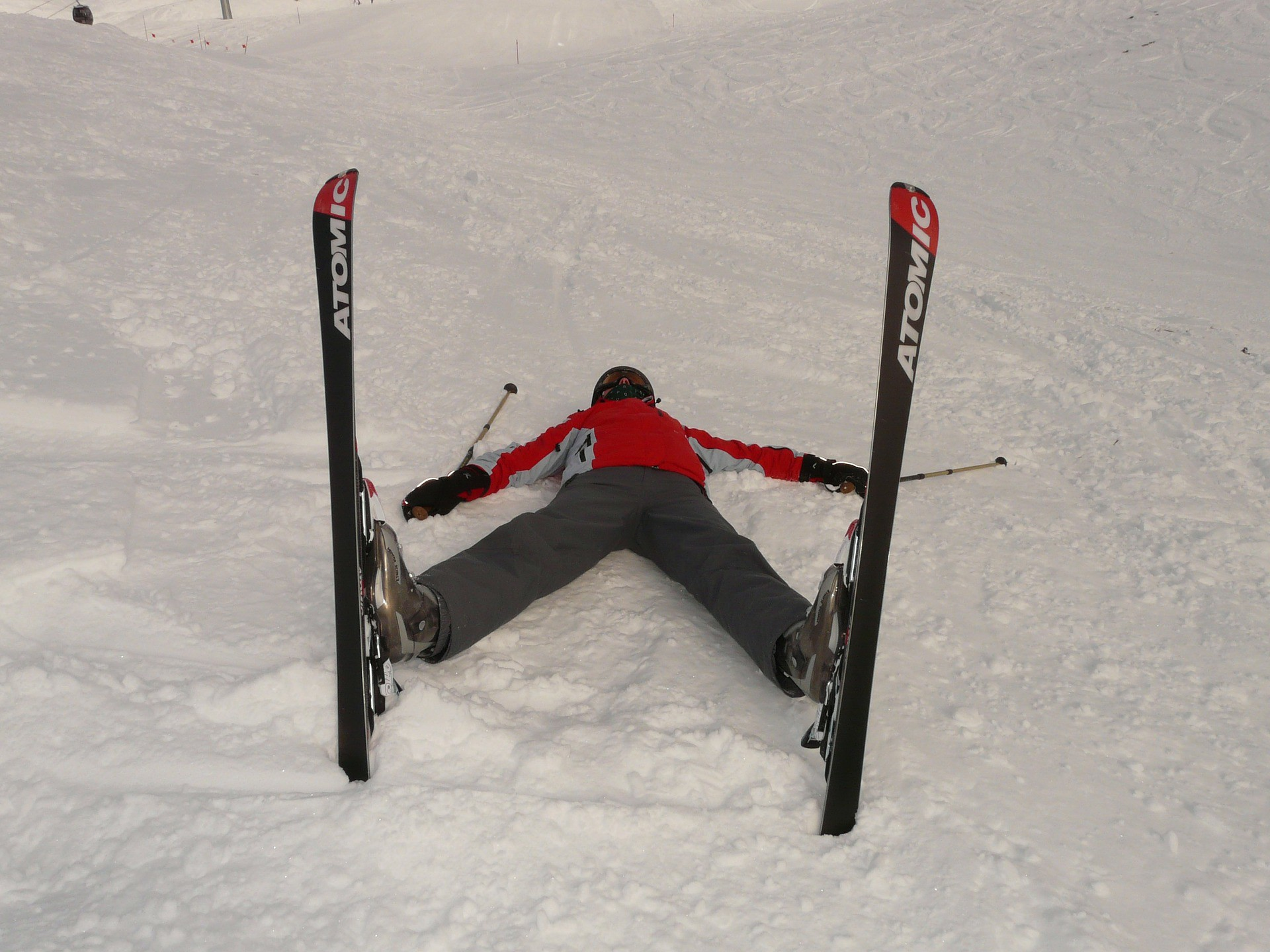 Skier laying on his back in the snow, spread-eagle and ski tips straight up