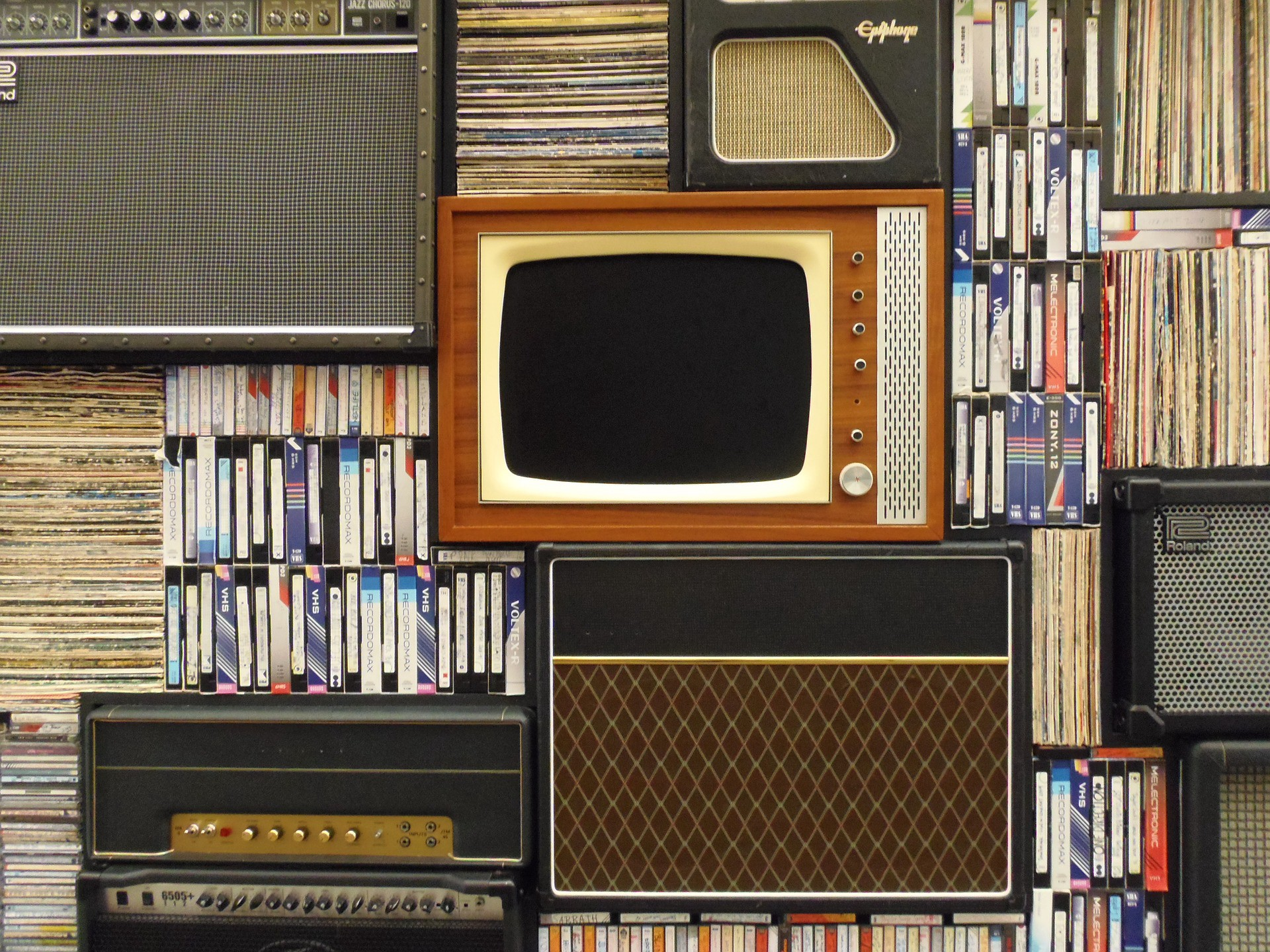 The image shows an old tv, music records, and vhs tapes.