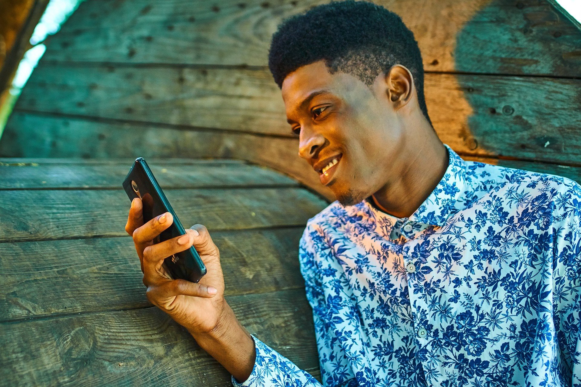 A gentleman holding his smartphone while smiling