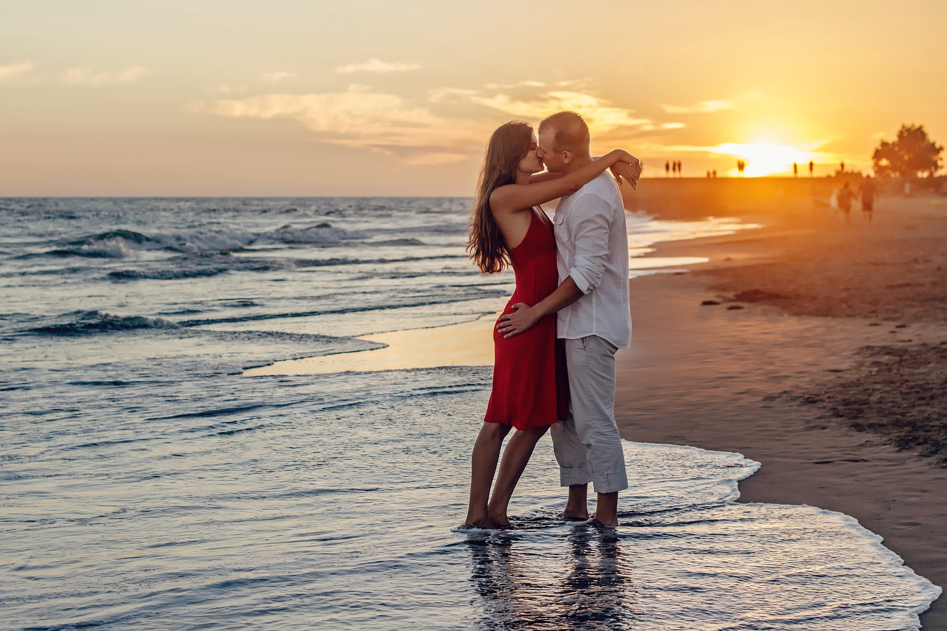 young man and woman kissing for the first time on a beach standing in the surf while the sun sets