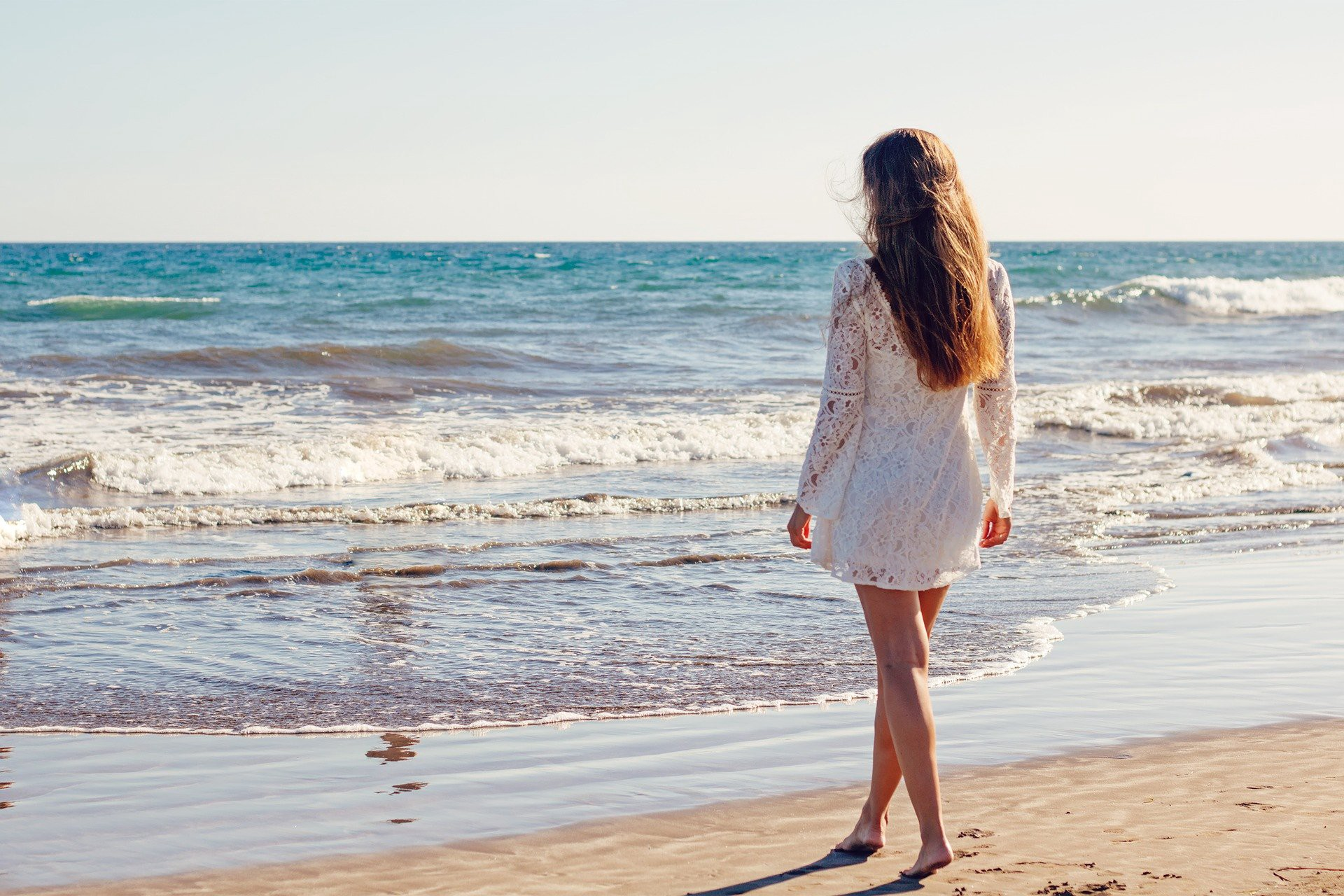 Woman on a beach looking out over the ocean. Why Is Finding Our Purpose Such a Struggle?