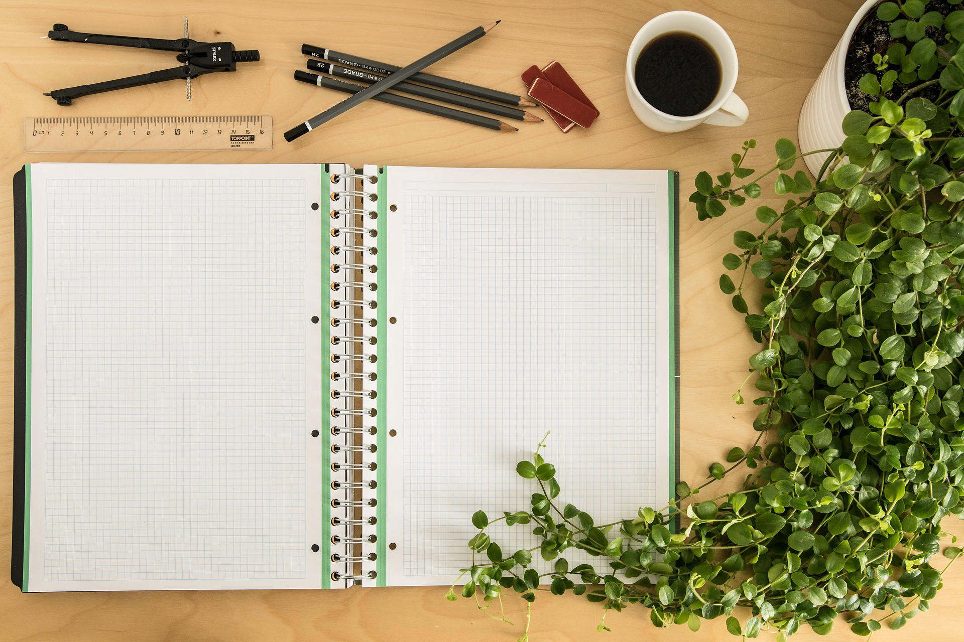 A blank notebook sits on a desk with a compass, ruler, pencils, coffee, and a potted plant.
