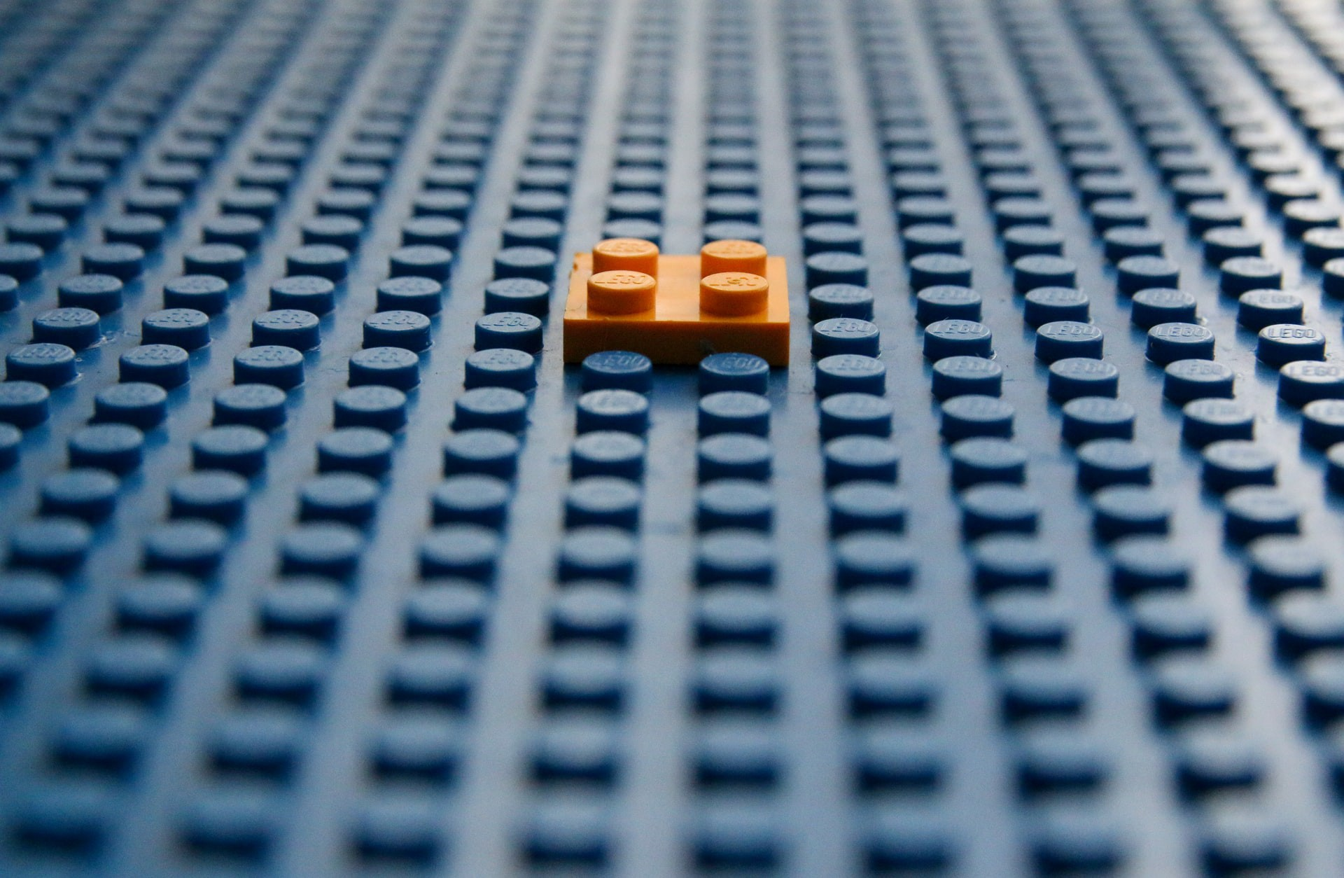 A tiny lego piece is placed on a lego board.