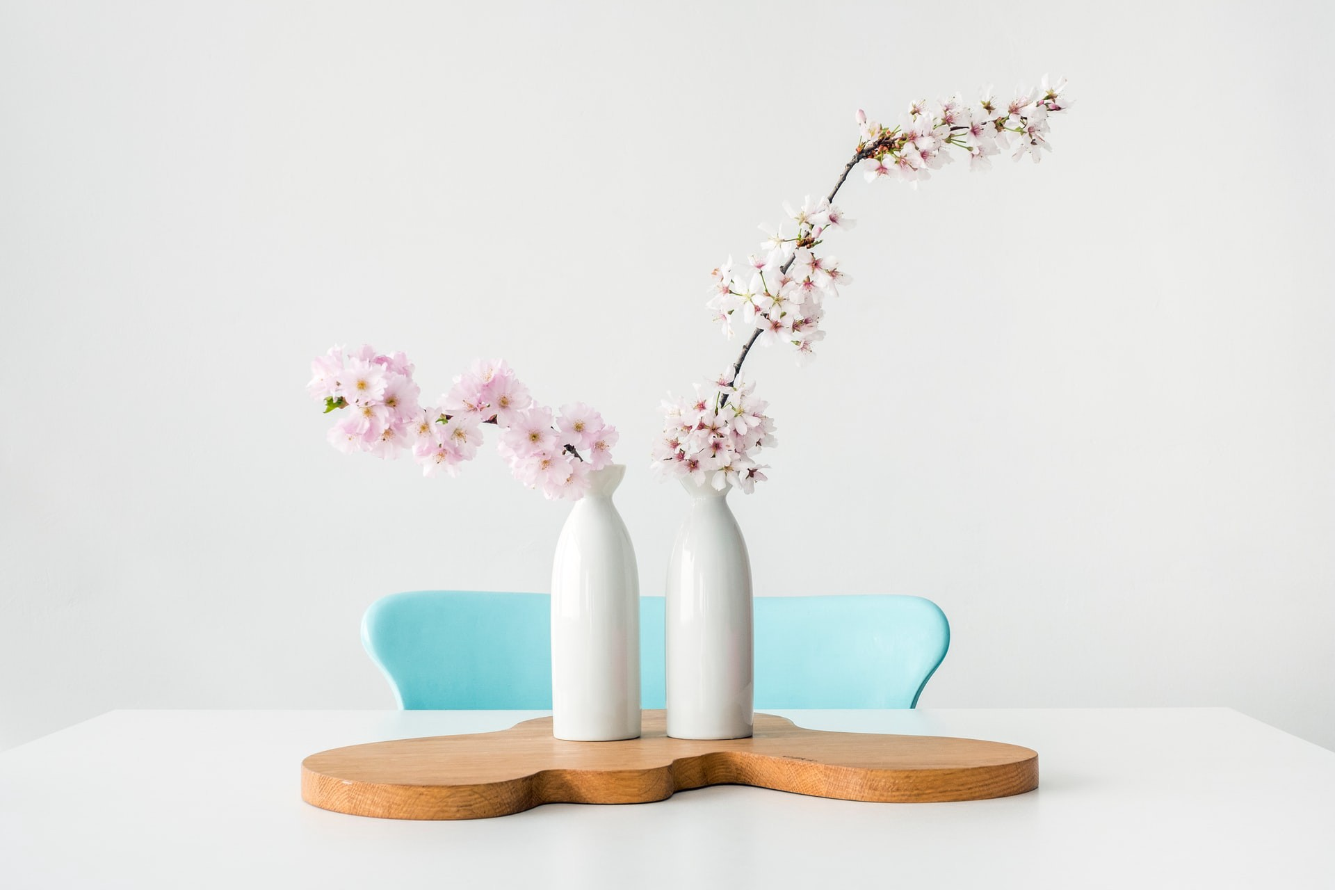 Two white vases with a stalk of flower each kept on a wooden board