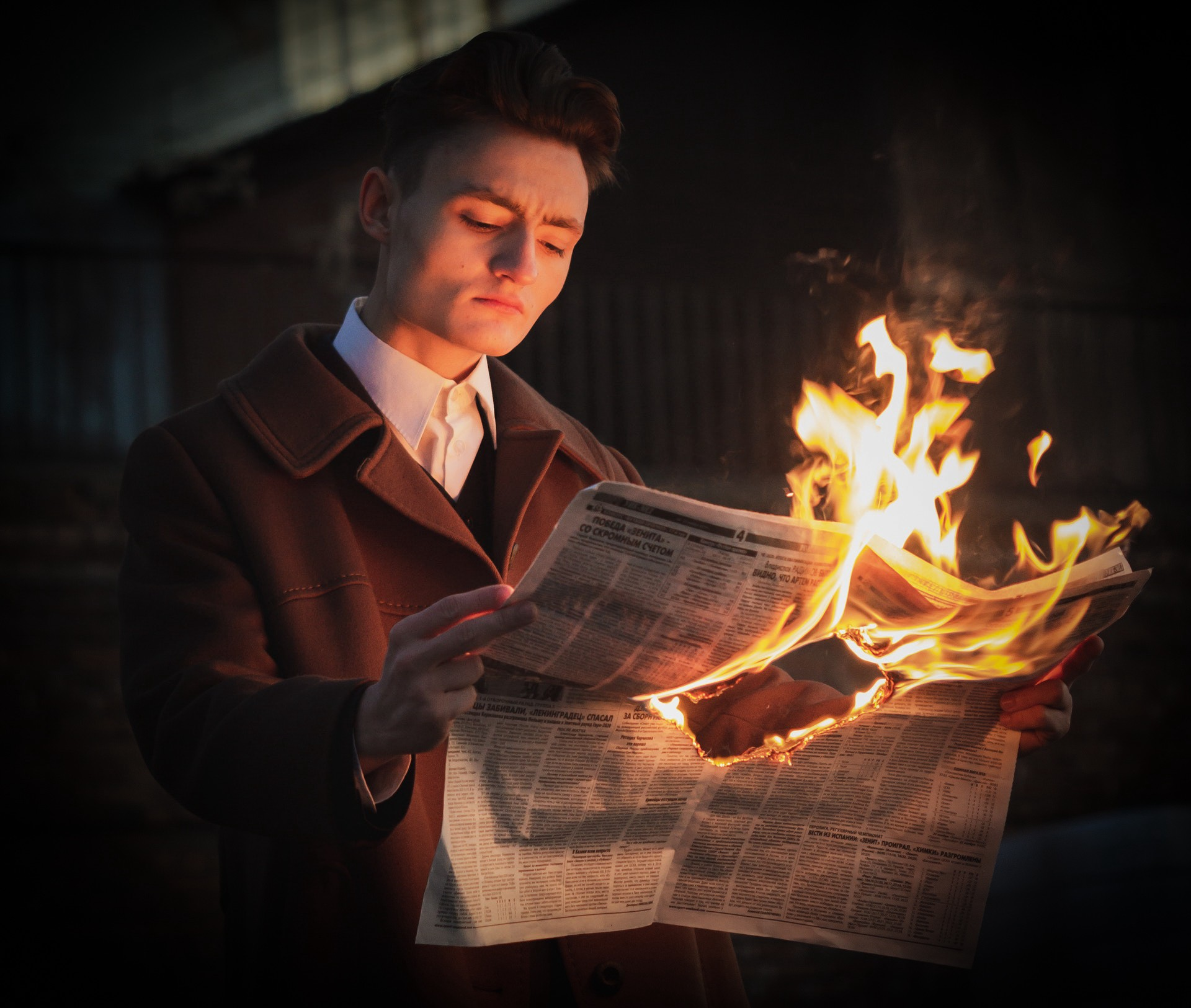 Studious man reading a burning newspaper in the dark. He'd better be quick!