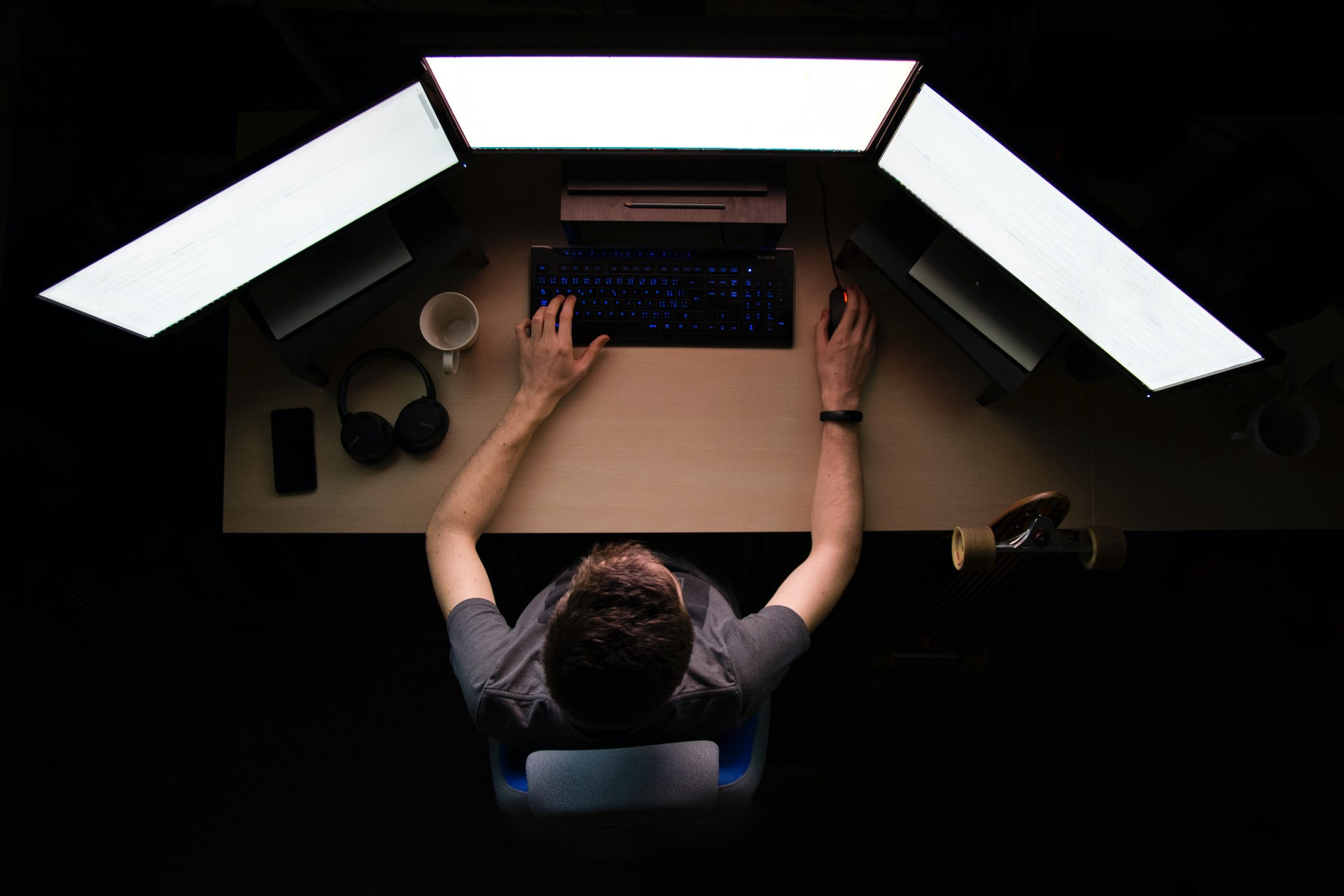 Dark room with man at computer surrounded by bright screens