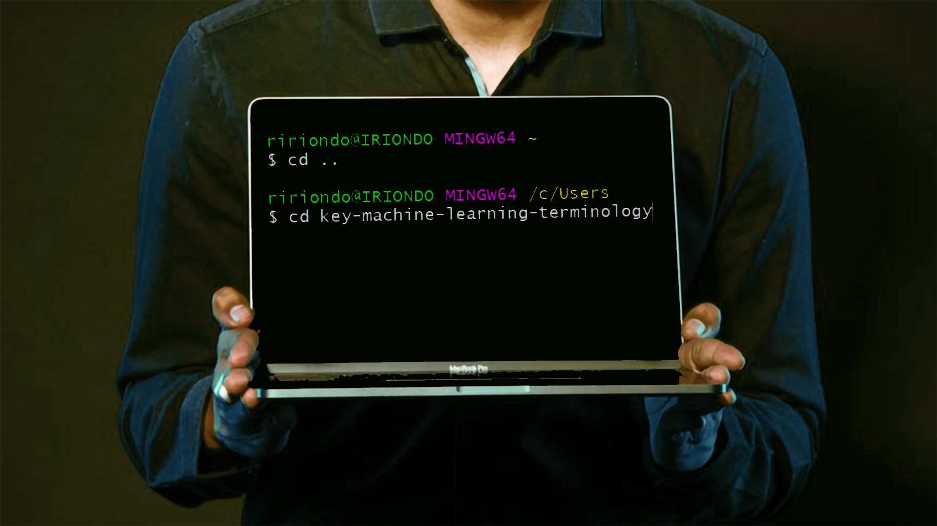 Person holding a laptop with a Git terminal screen saying key machine learning definitions