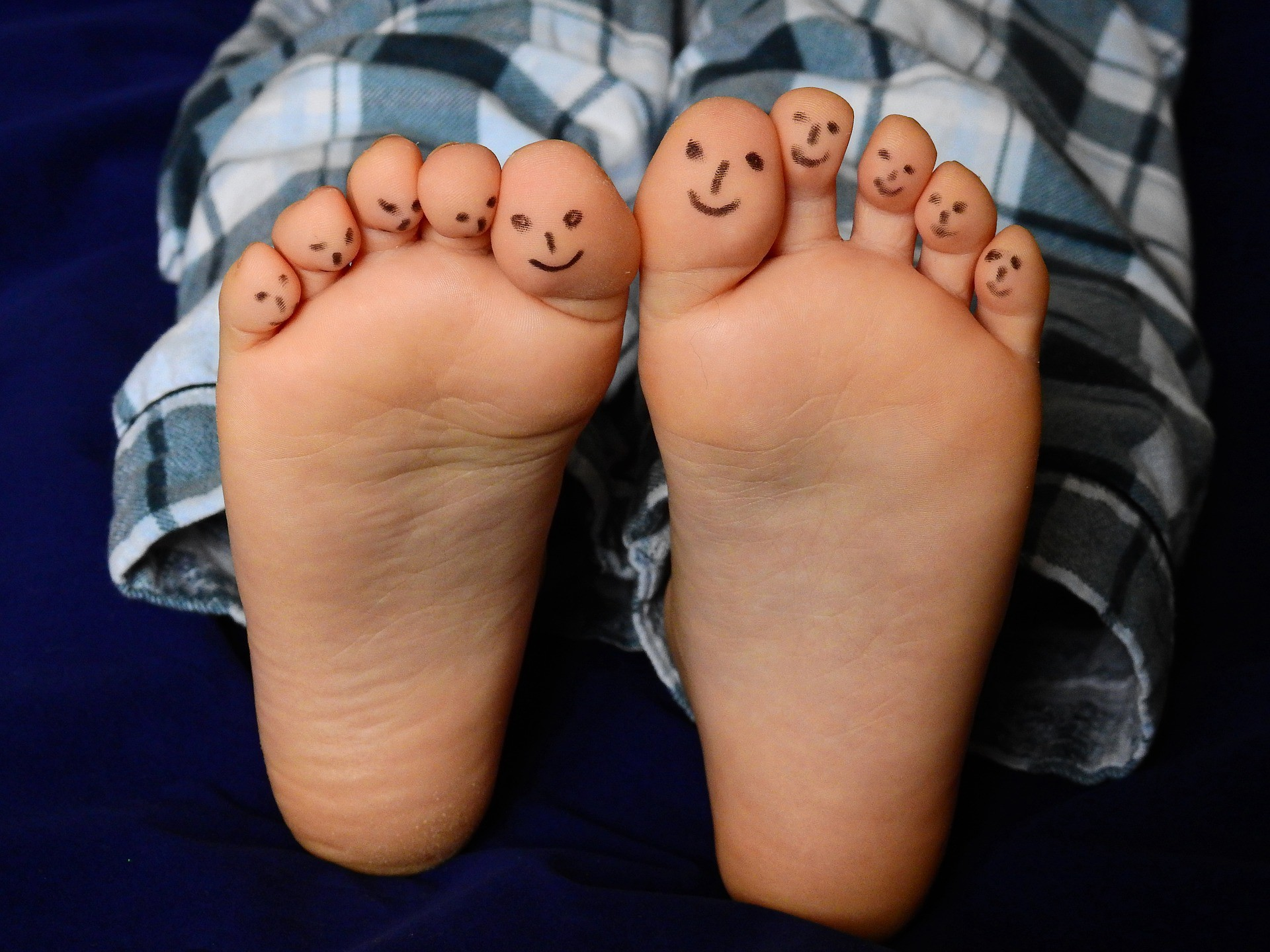 Photo of a child's feet with black marker drawings of happy faces on each of their toes. Child is wearing black plaid pajamas