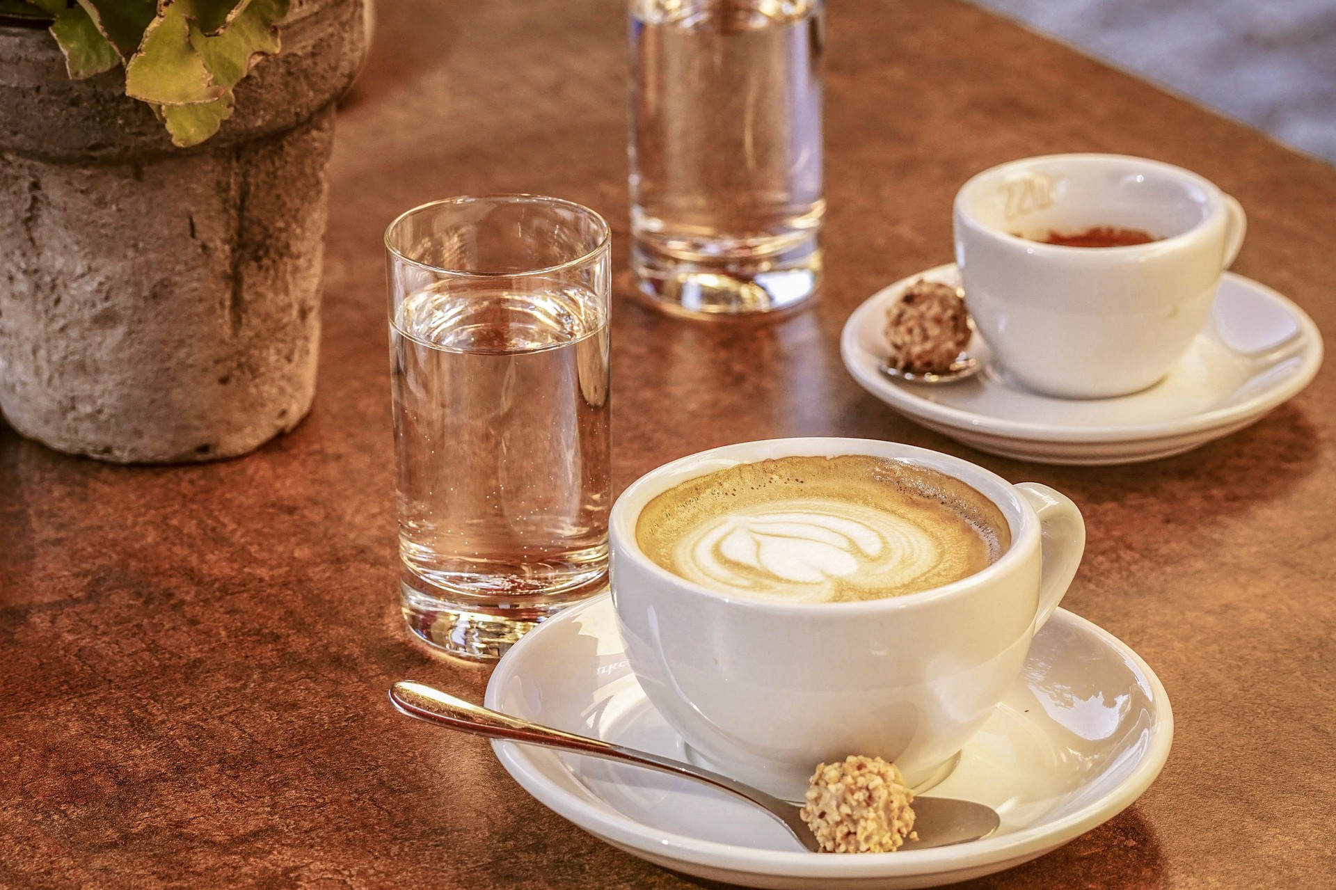 A glass of water and a cappuccino on a wooden table.