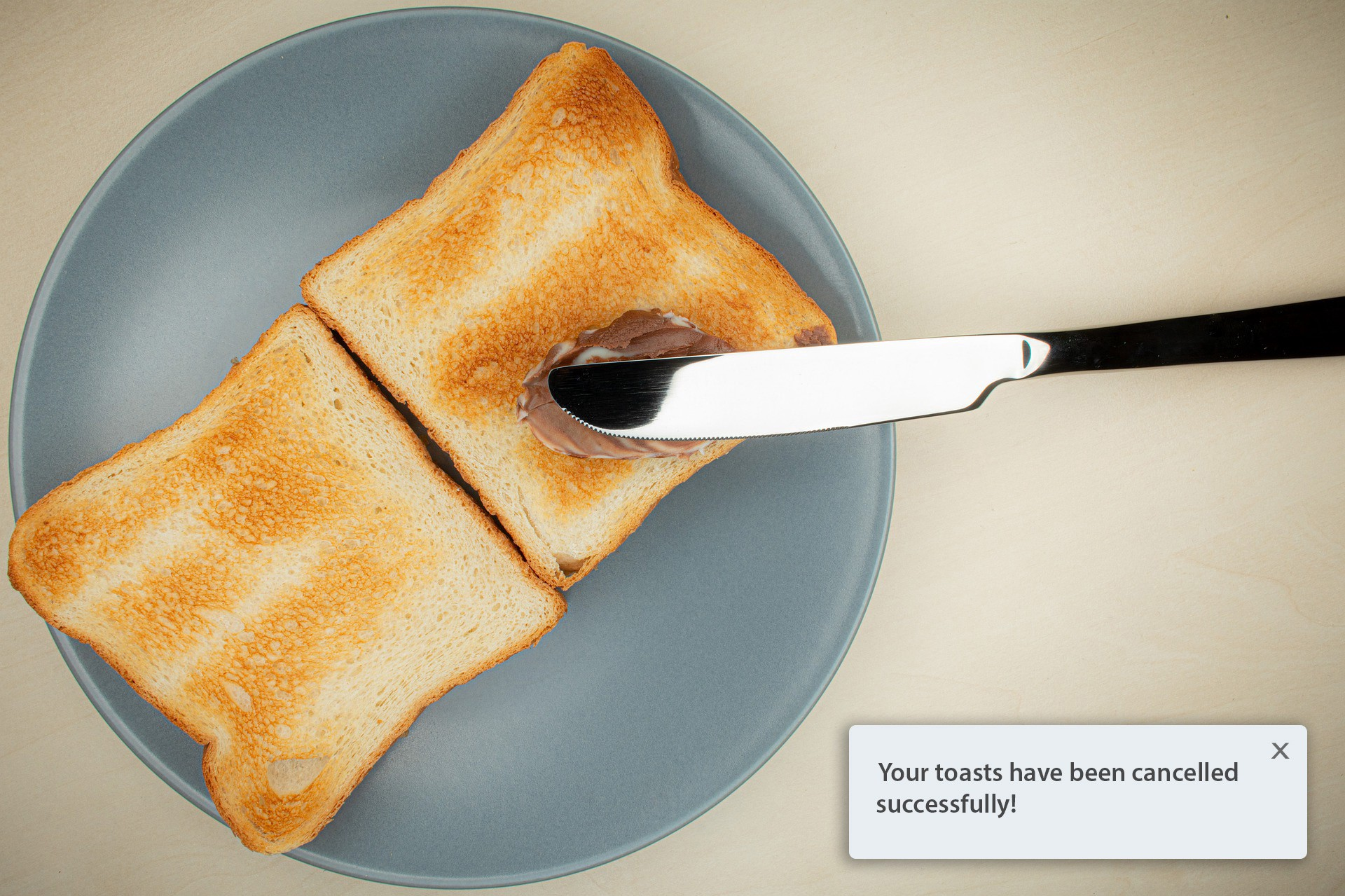 Two slices of toasted bread, a knife and some Nutella. A toast notification in the bottom right corner.