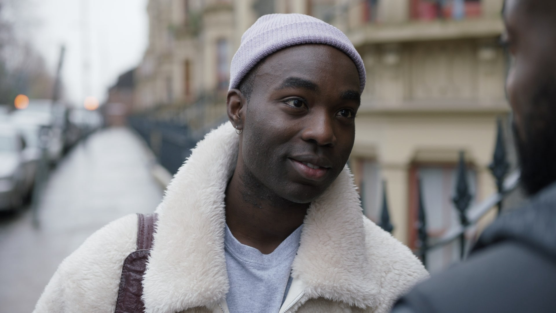 Kwame with furry coat and beanie.