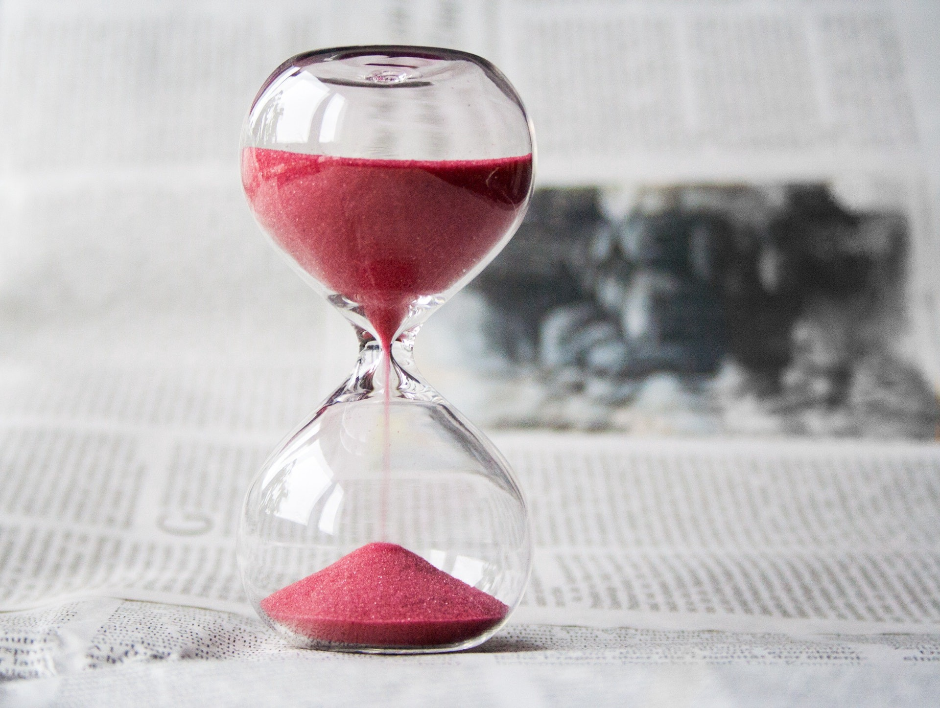 A clear hourglass with red sand.