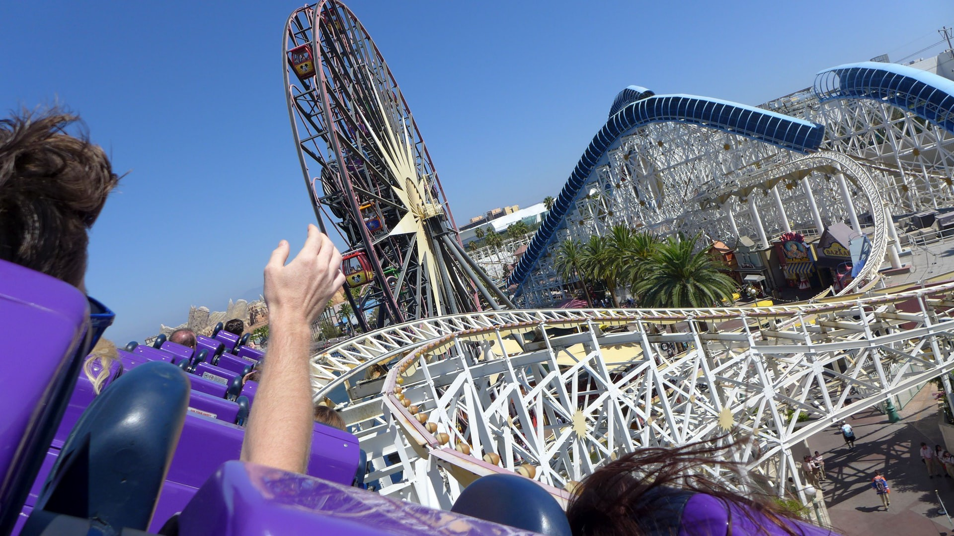 A human hand raised into the air as the human faces an unwinding roller coaster ride.