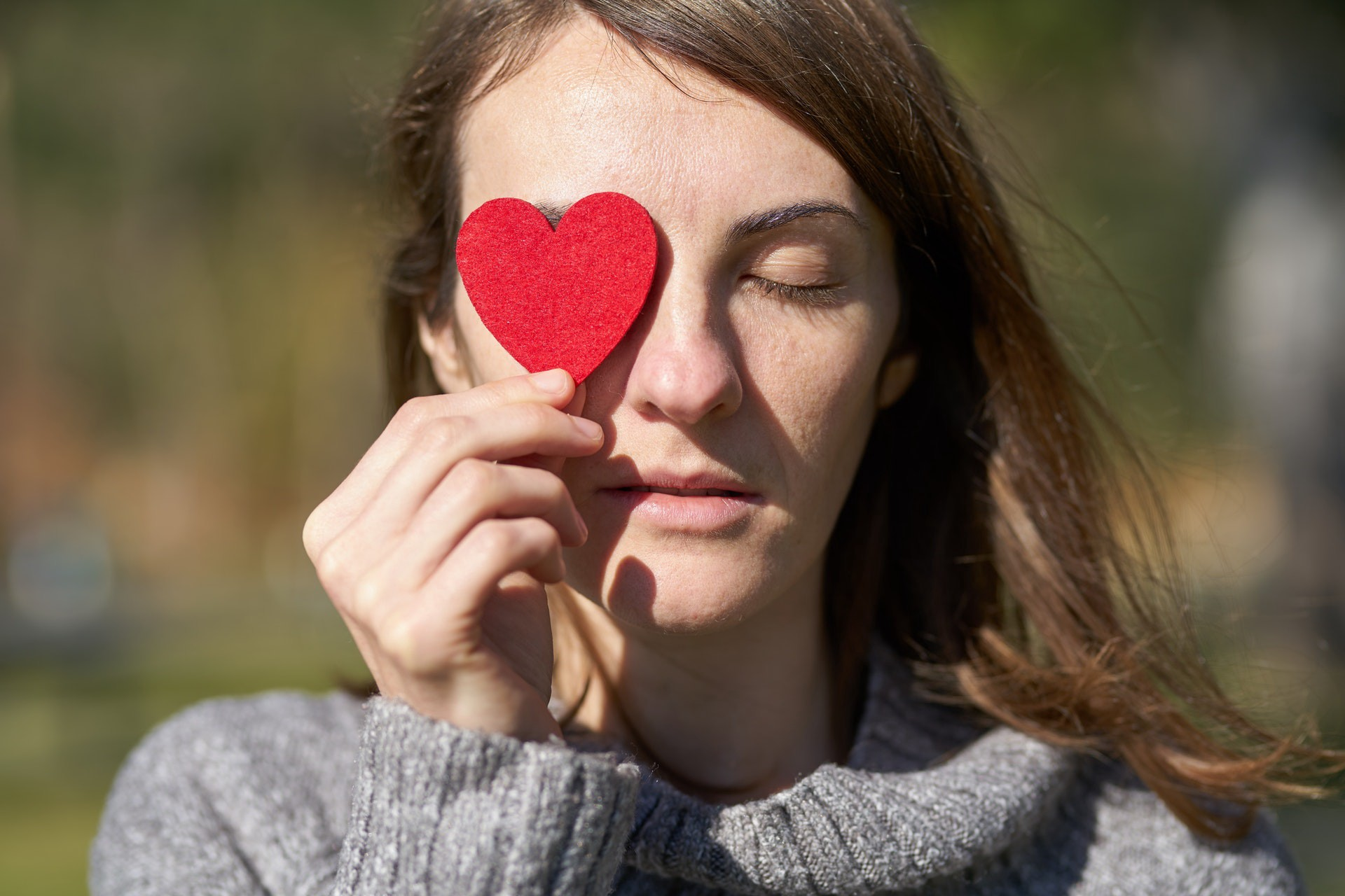 Woman holding a heart-shaped fabric over her right eye