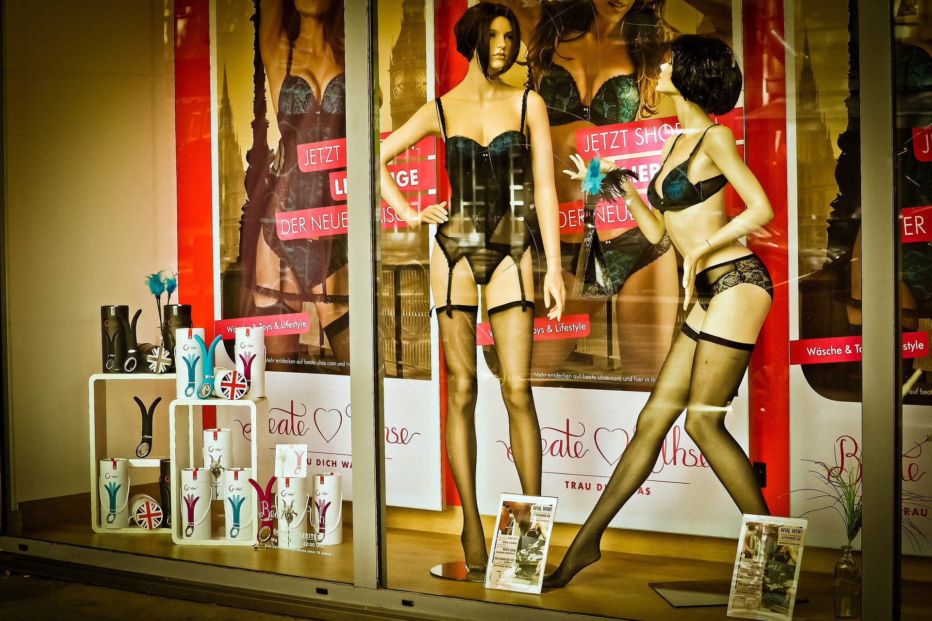 View of an adult sex shop window with mannequins in underwear and sex toys on display