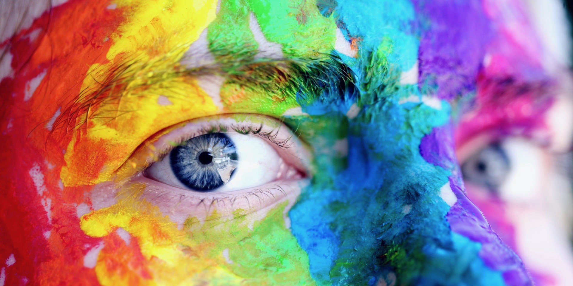 Close on a pair of eyes in a face splattered with rainbow paint