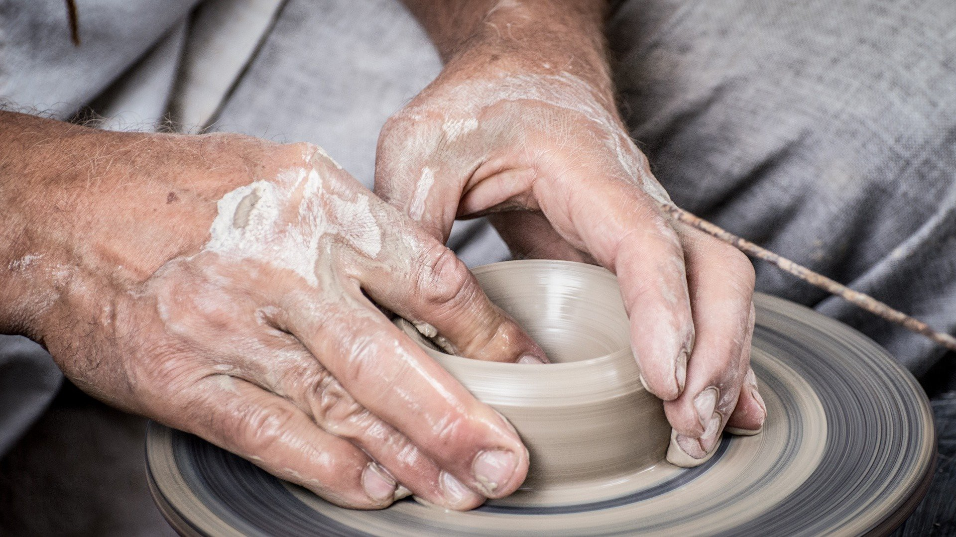 A potter's hands turn a cup or bowl on a potter's wheel.