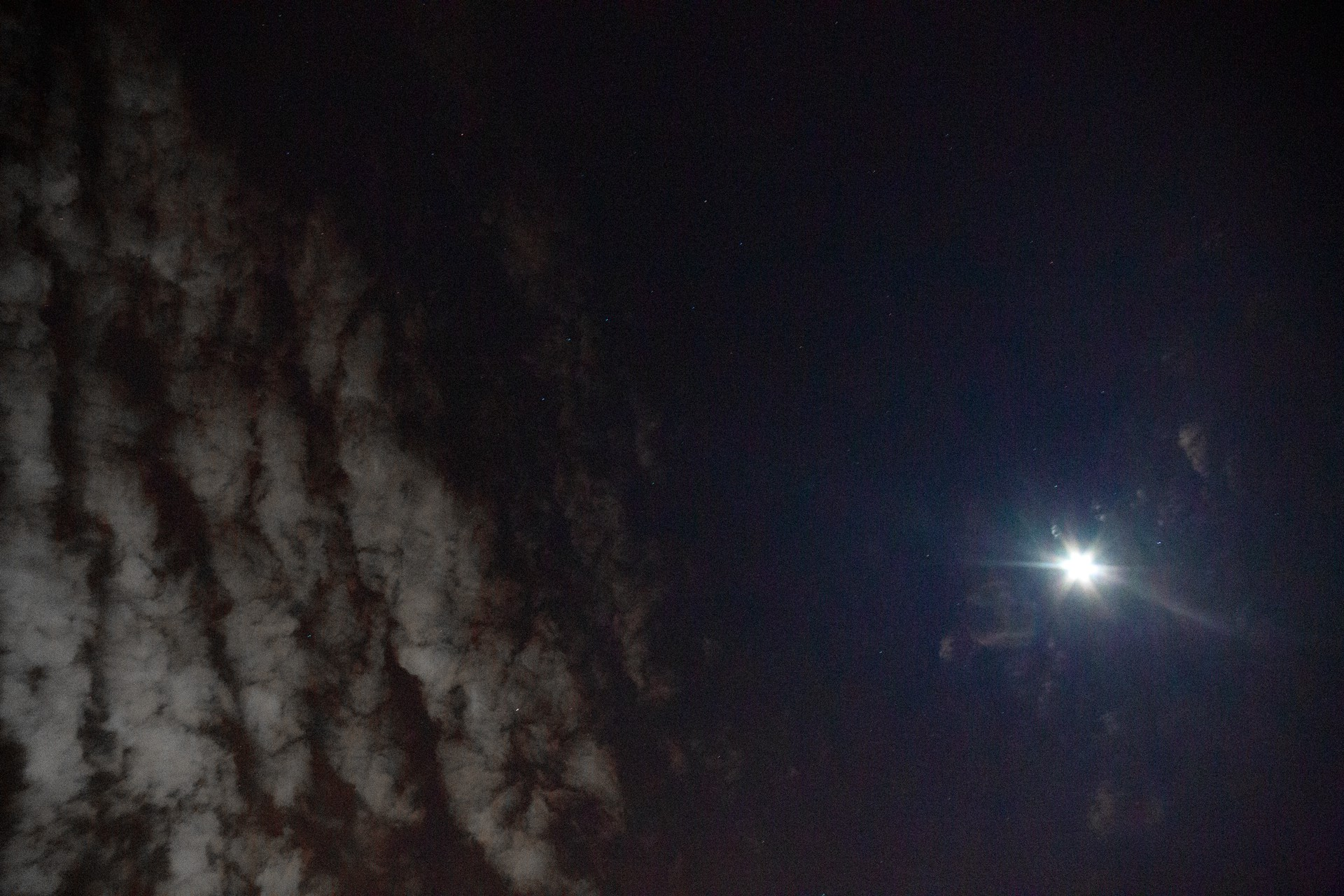 Photo of the moon in the night sky with clouds passing by the far left side. Photo by Matt Cannon, Taken April 4th, 2020