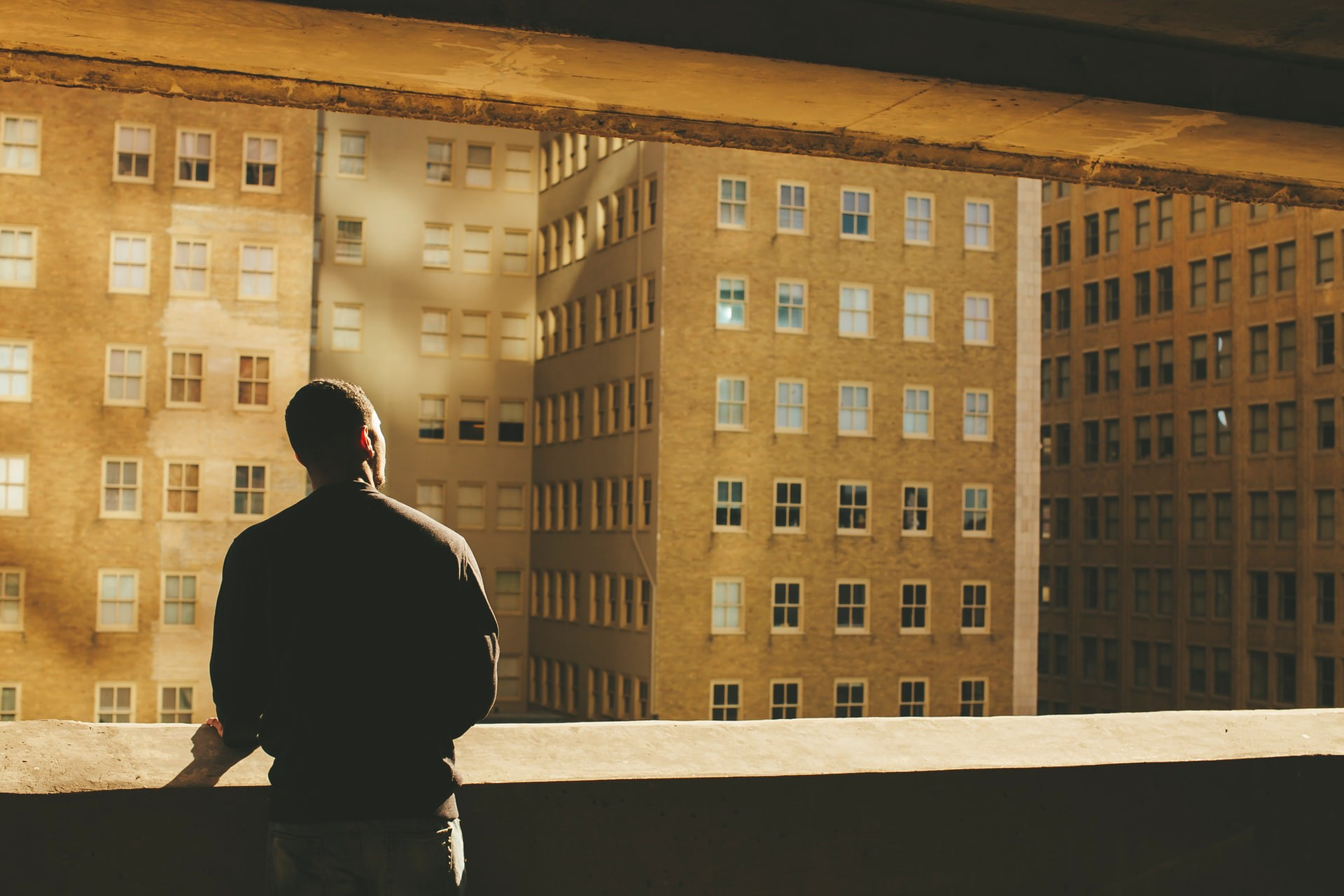 Man at the window looking at other buildings