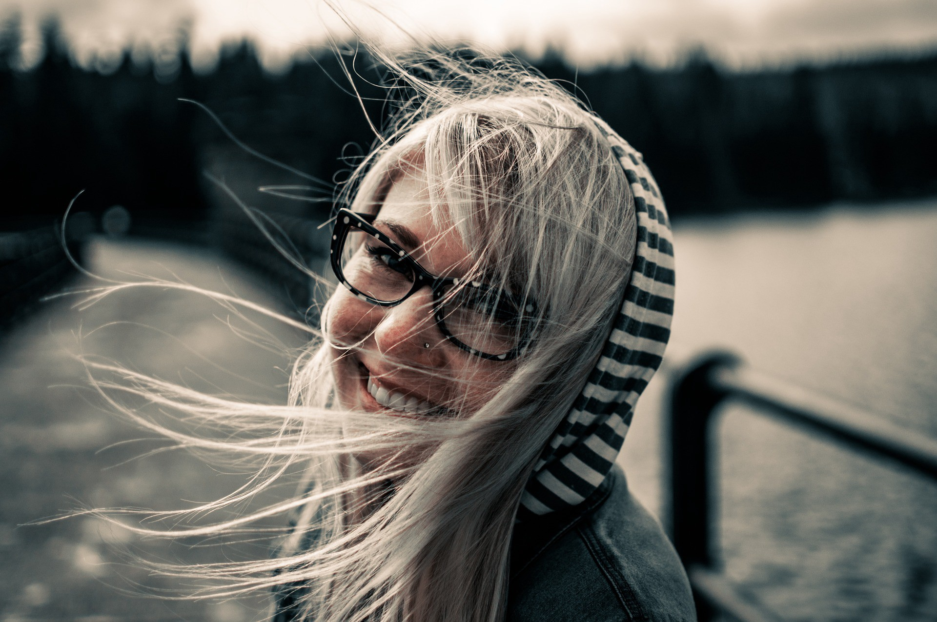 Smiling woman with her hair blowing by a lake. How Using Your Personal Power Can Change the World.