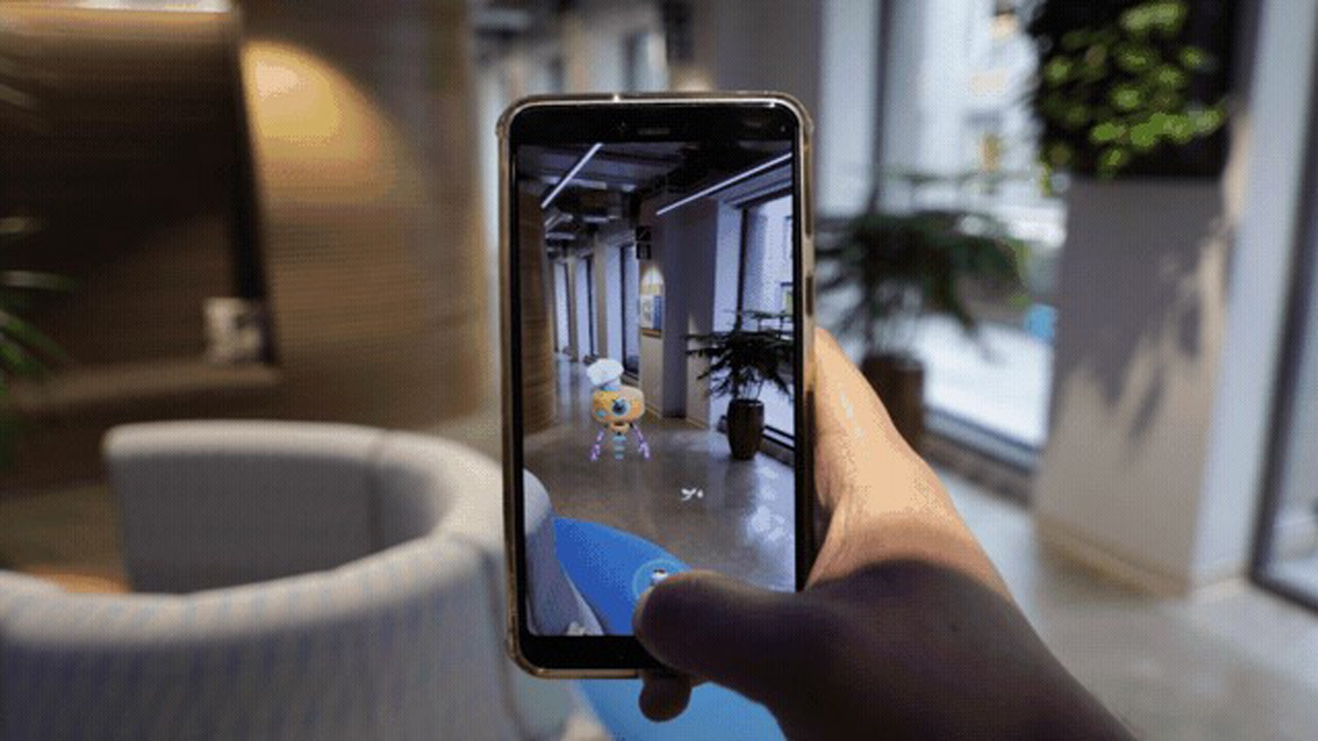 A hand holding up a smartphone, on which a digital character is seen in augmented reality