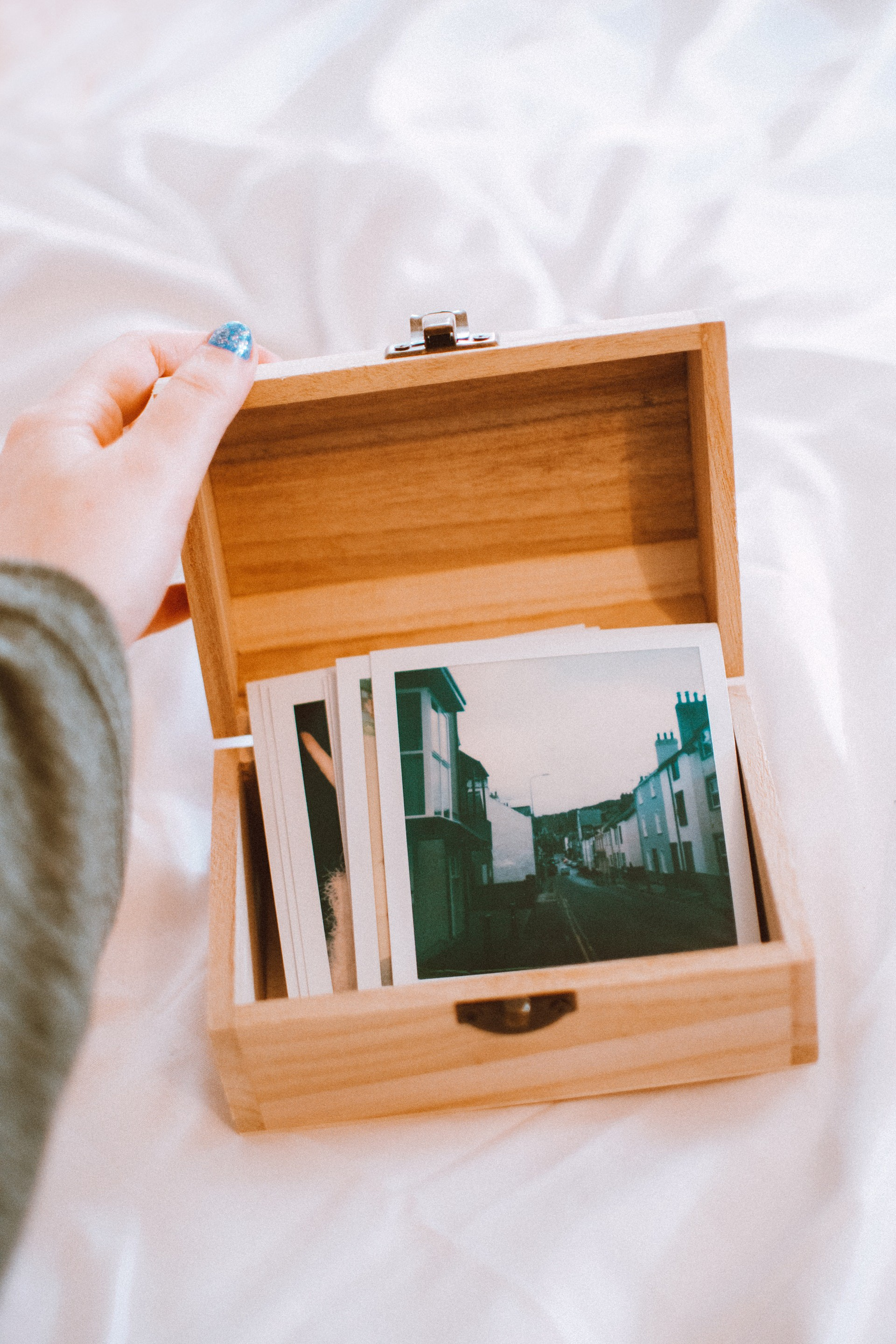 Hand opening wooden box of photographs