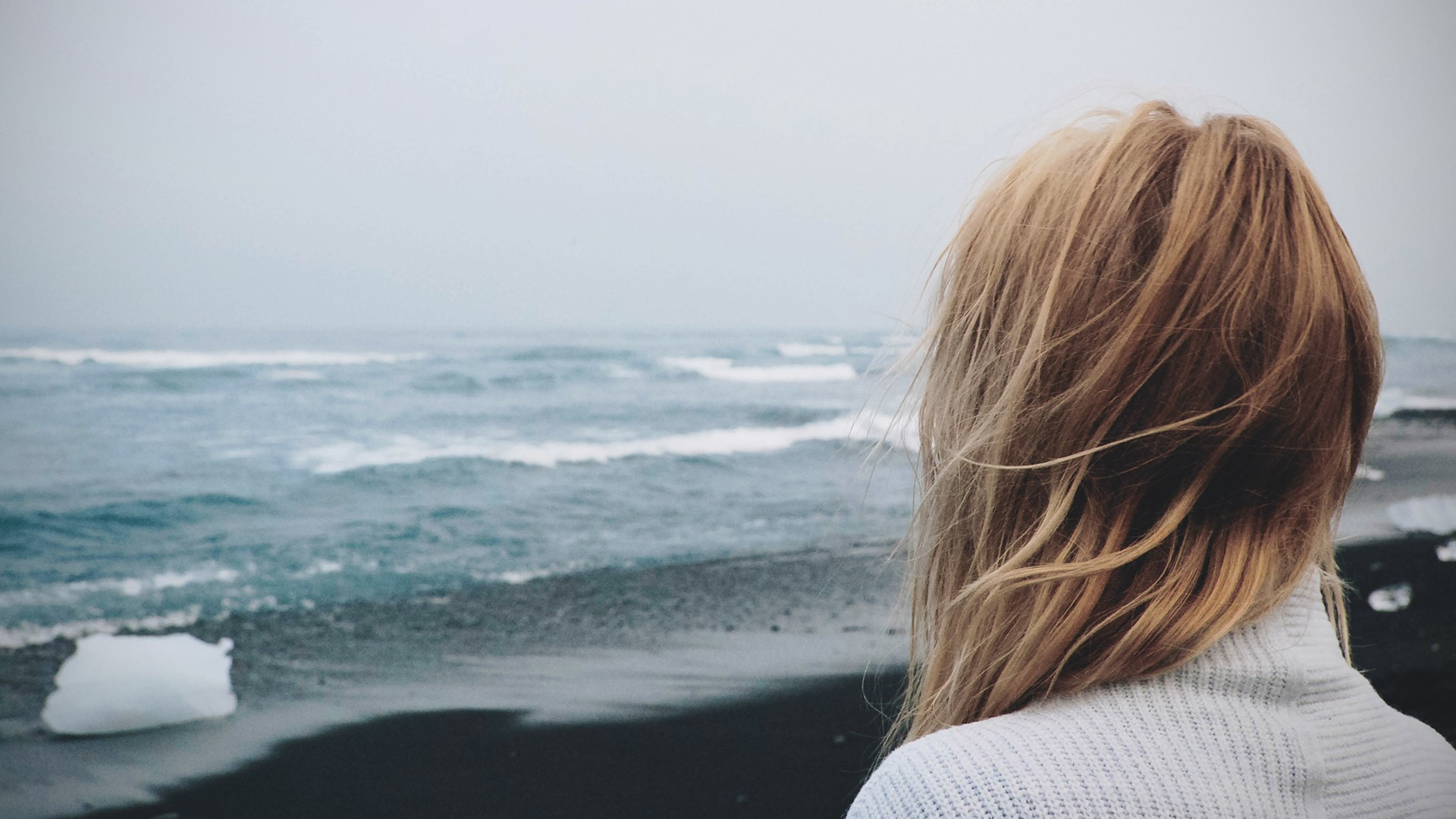 A blonde woman stands with her back to the camera, facing the sea