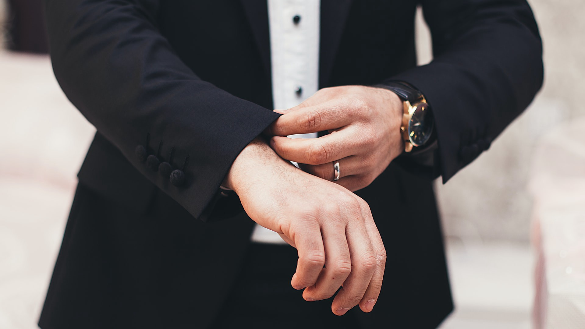 A man in a suit wearing an expensive watch adjusts his sleeves