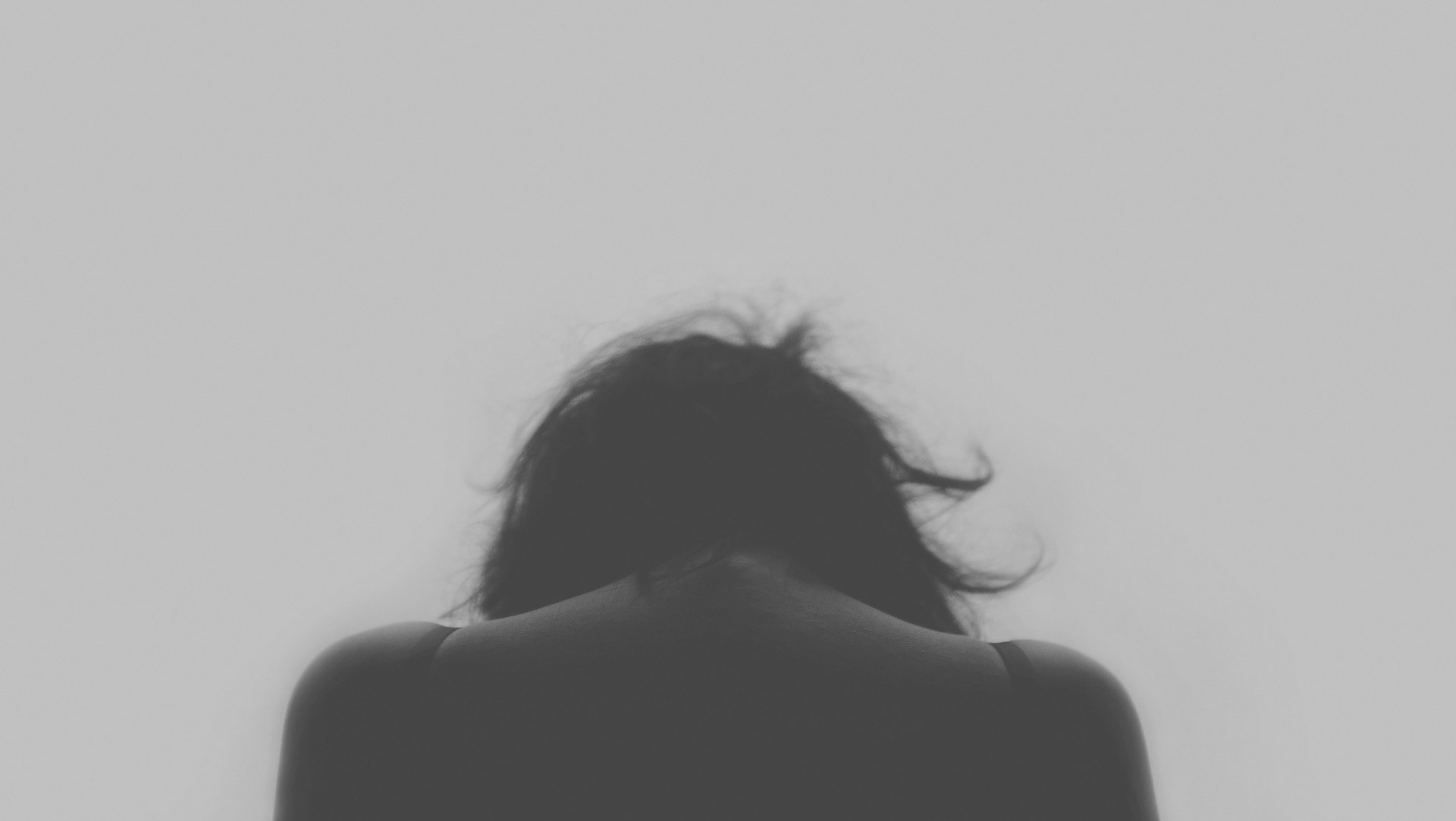 A black and white photograph of a sad woman facing away from the camera. Her head is lowered.