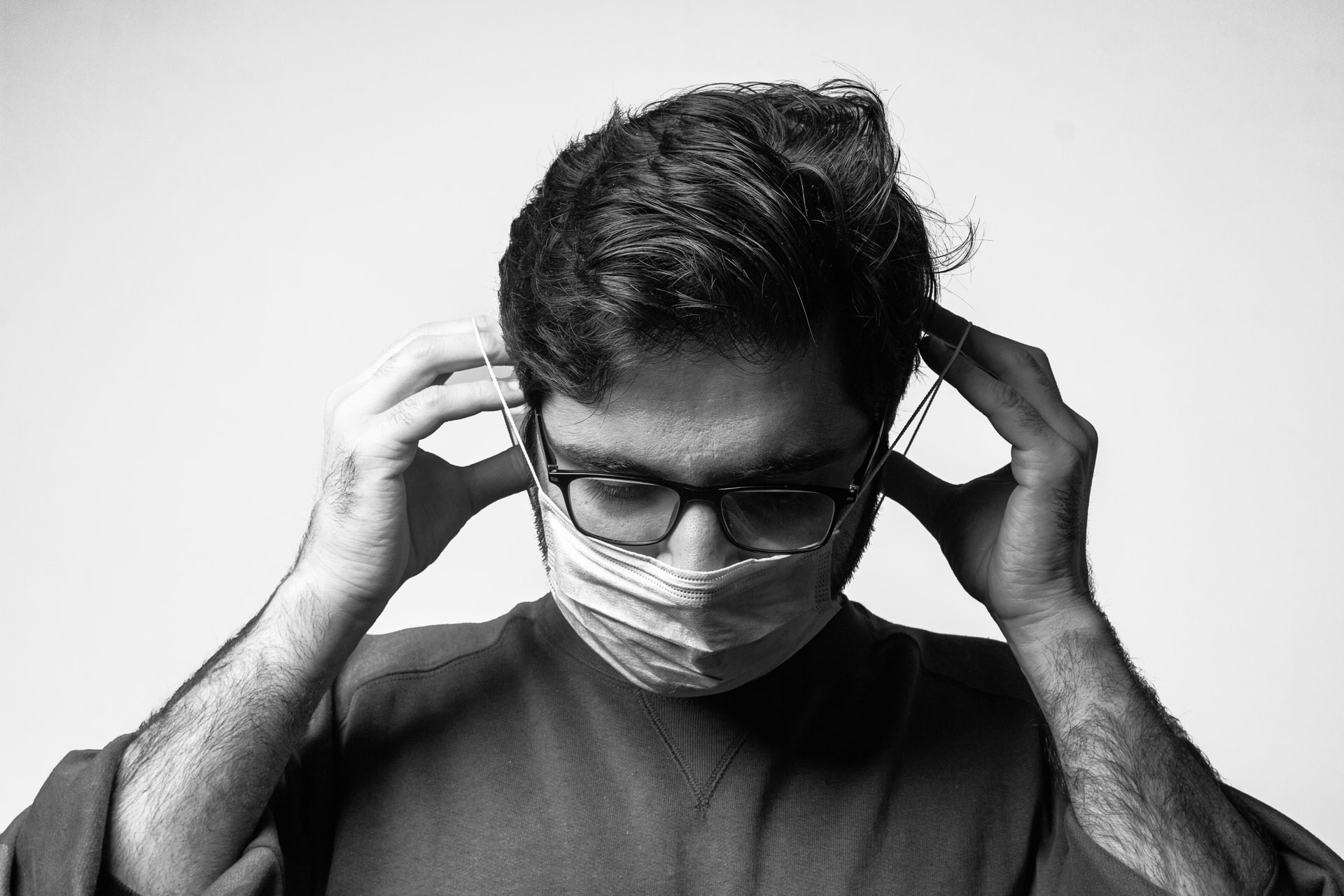 Man putting on face mask. Black and white photo.