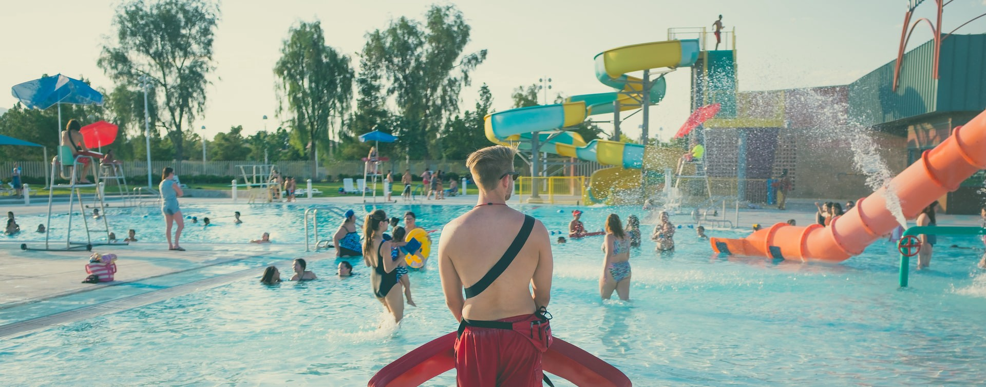 Lifeguard in red shorts stands watching swimmers in a public outdoor pool.