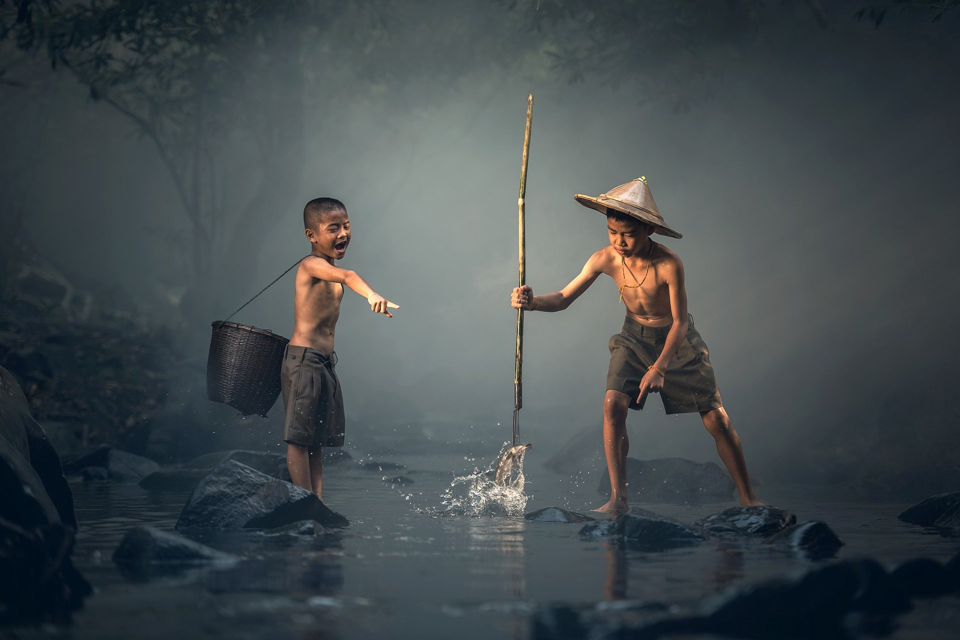 Two Asian children trying to catch fish