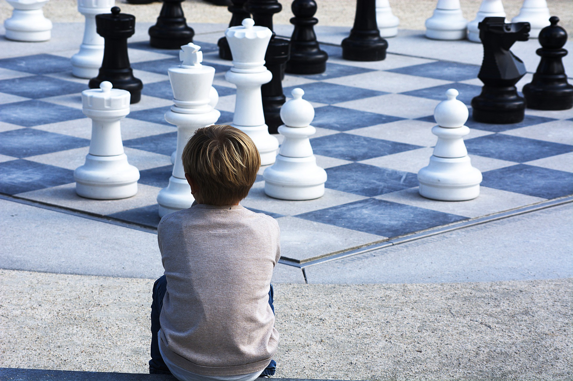 Boy sitting on a concrete barrier looking at a giant chessboard with black and white chesspieces