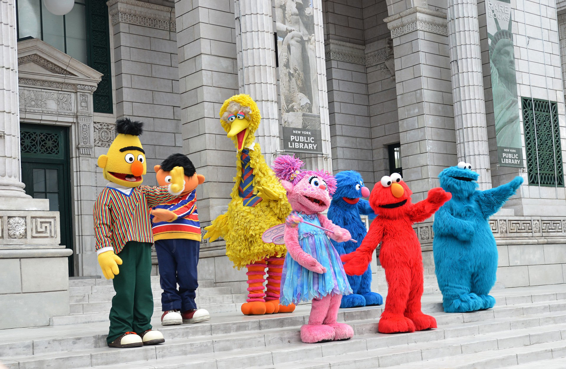 Beloved characters from the hit TV show Sesame Street wave from the steps of the New York Public Library.