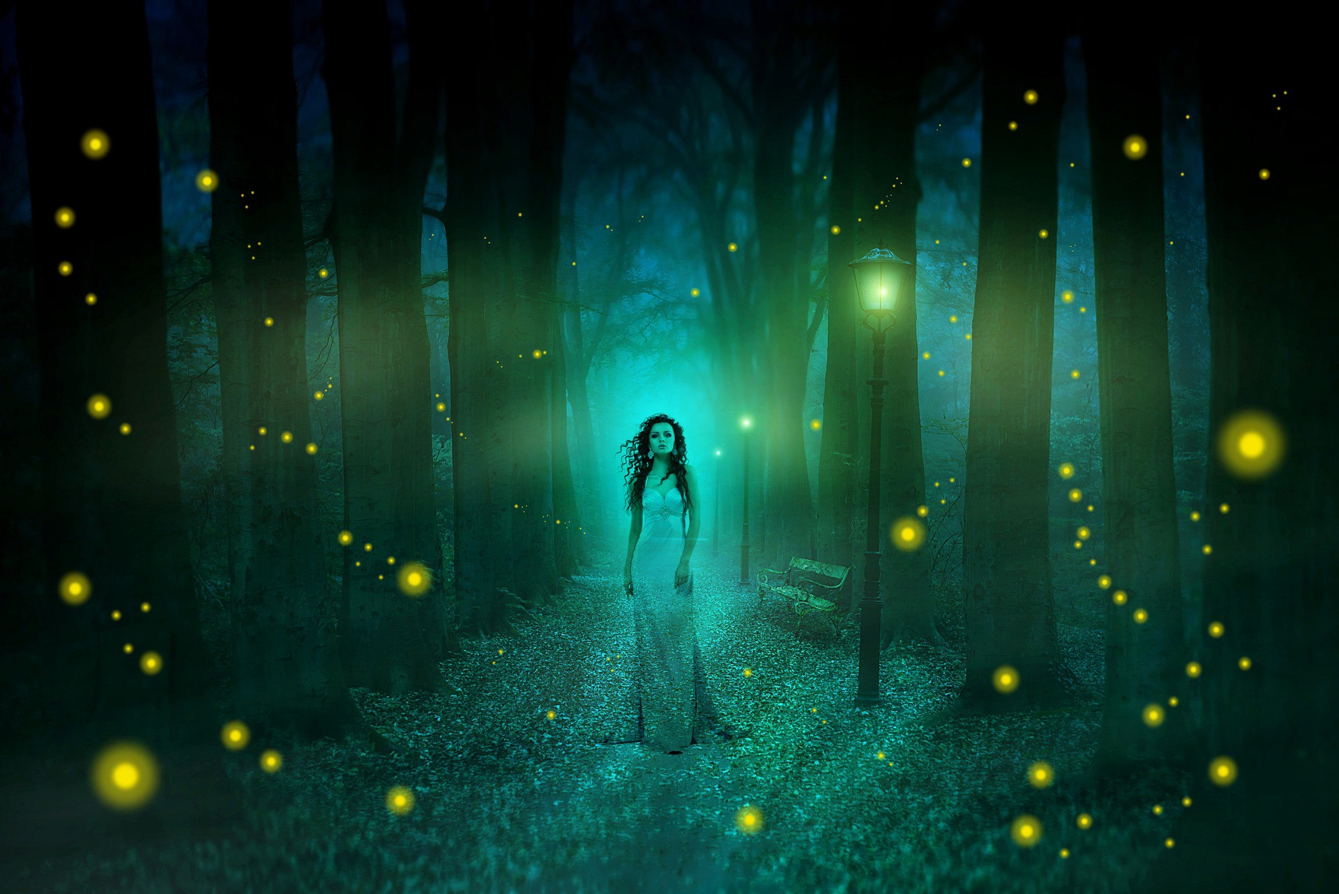 Ethereal woman in woodland at night, lit with fireflies