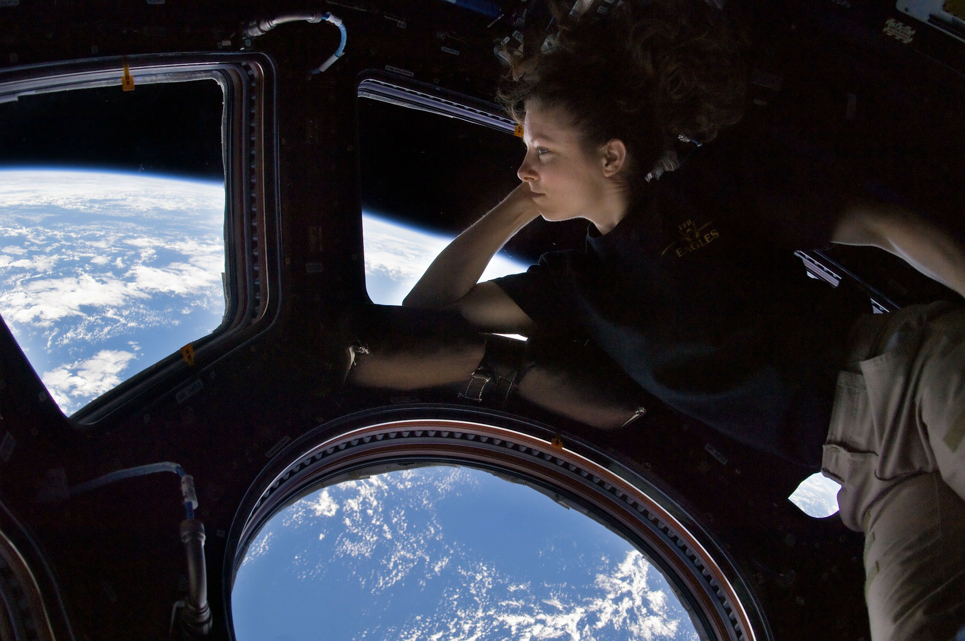 An astronaut gazes at Earth from a window of the International Space Station.