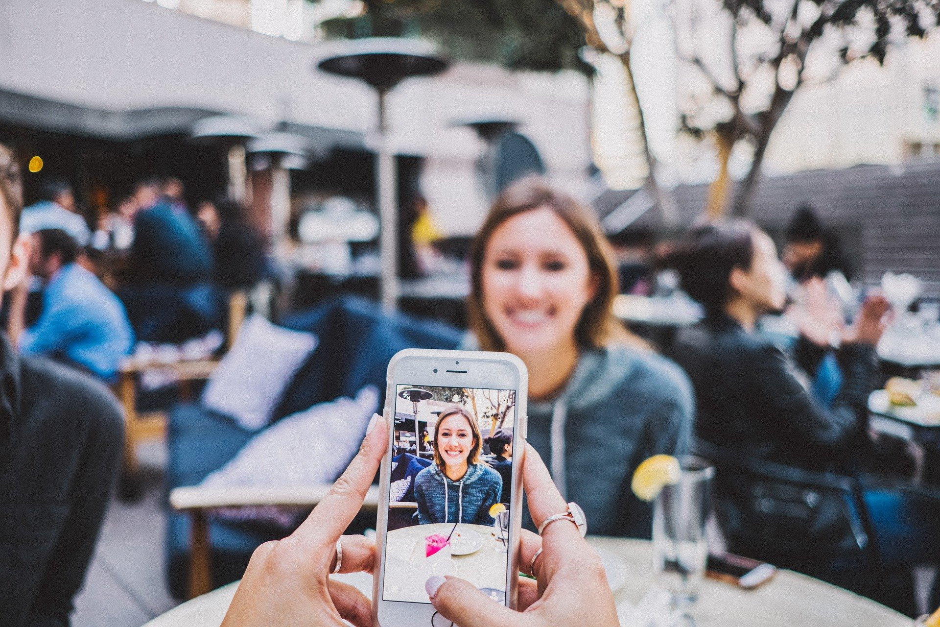 A person takes a photo of their friend with their phone. They are sharing a meal at an outdoor restaurant.